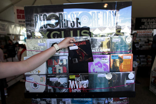 "A Zia Records employee pulls a 7"" vinyl version of Jimmy Fallon's ""Tebowie"" at their onsite location on Record Store Day, the second day of week two of the Coachella Valley Music and Arts Festival in 2013."