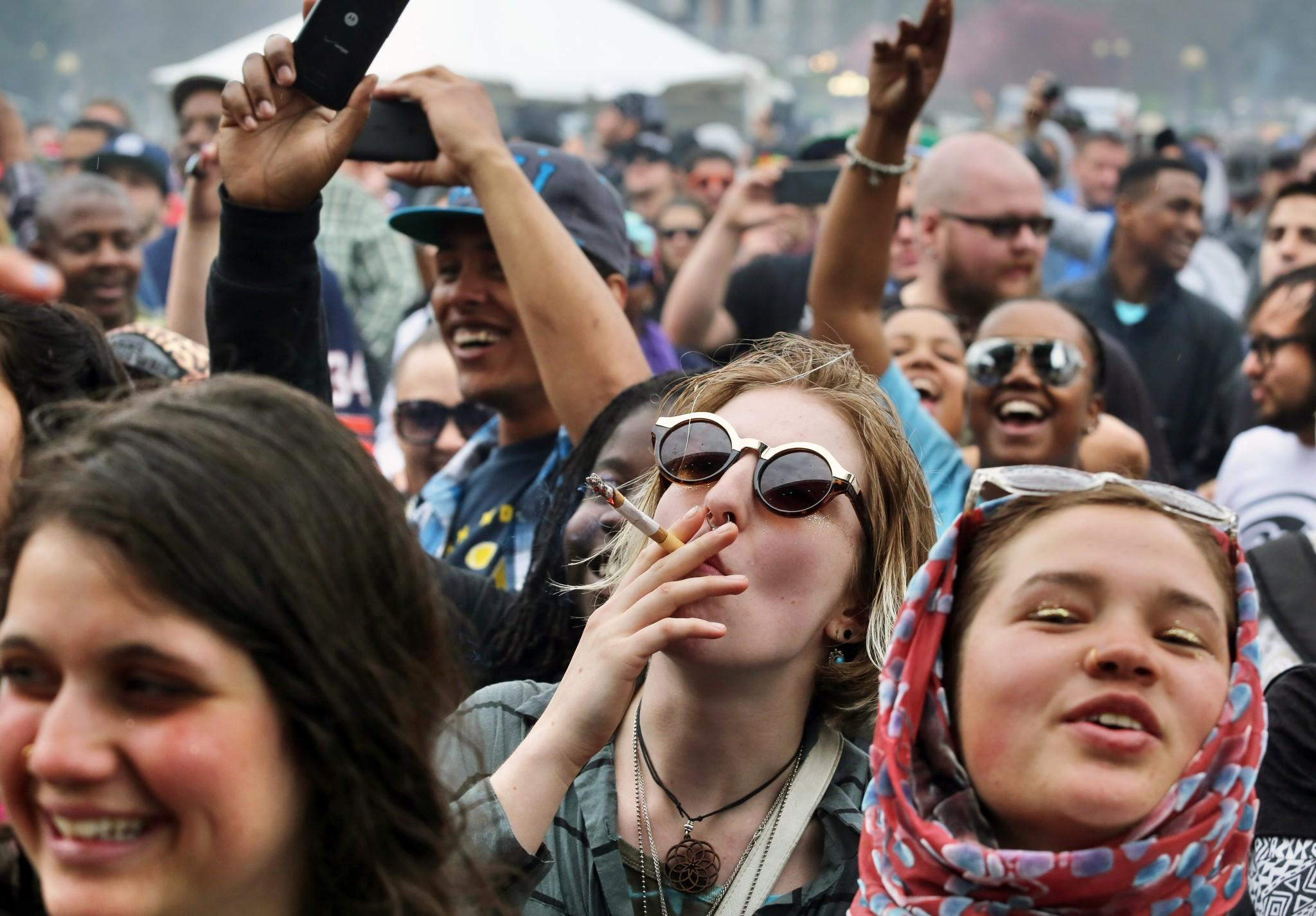 With the Colorado state capitol building visible in the background, party-goers dance to live music and smoke pot on the first of two days at the annual 4/20 marijuana festival in Denver on Saturday. The annual event is the first 420 marijuana celebration since retail marijuana stores began selling in January.