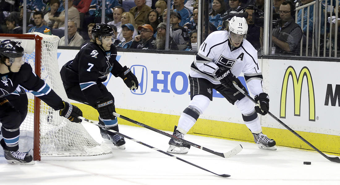 Kings center Anze Kopitar (11) maneuvers behind the net as Sharks defenseman Brad Stuart (7) pursues the play during the first period of Game 1 on Thursday, in San Jose.