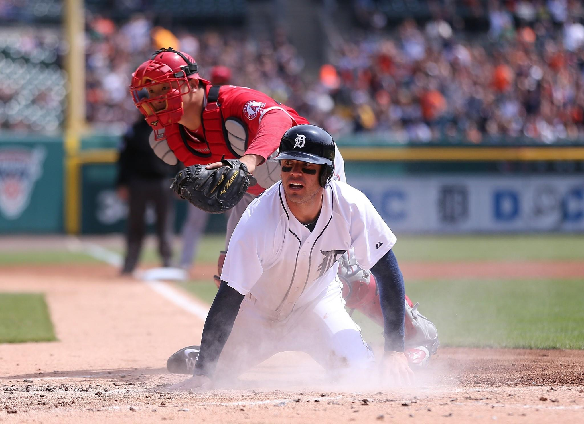 Tigers second baseman Ian Kinsler is safe at the plate after a series of throwing errors in the first inning Sunday in Detroit.