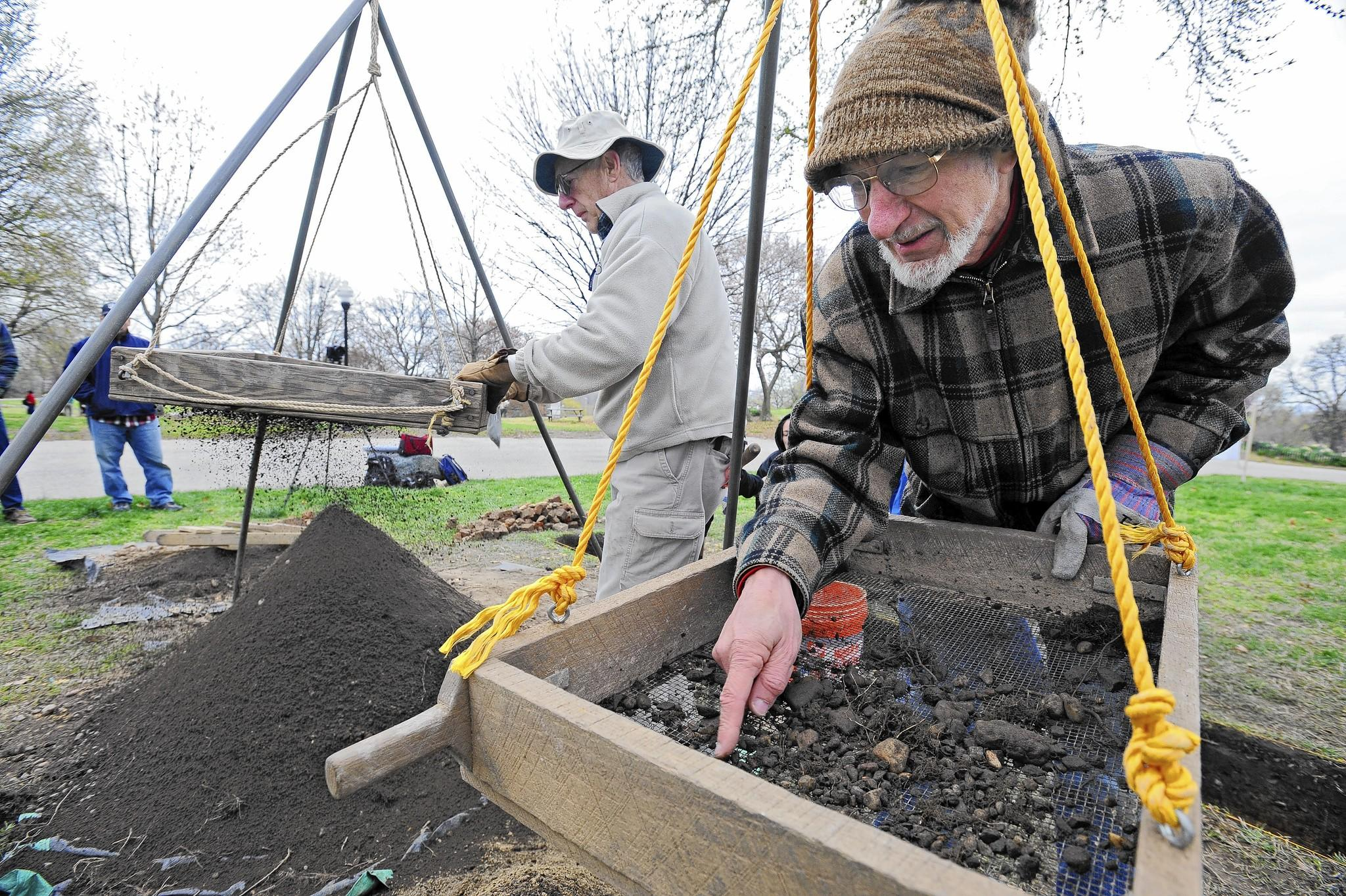 Volunteer Stephen Israel, right, of Catonsville, looks through dirt for any possible artifacts.
