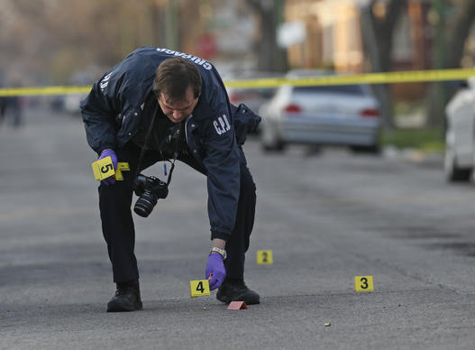 A Chicago Police department evidence technician sets up markers near the casings while investigating the scene of a shooting on Hermitage avenue and 85th Street.