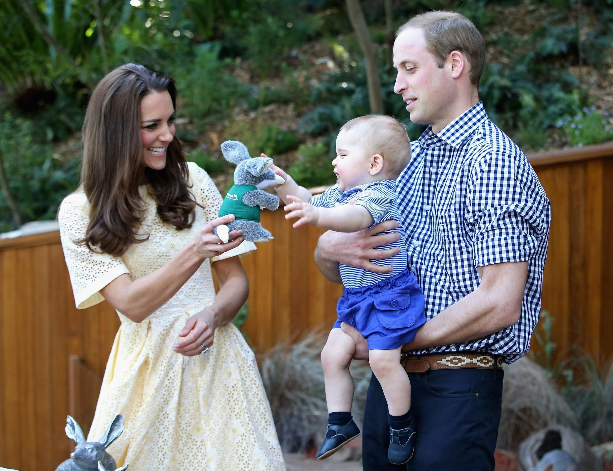 Prince William, Duke of Cambridge, holds Prince George of Cambridge as Catherine, Duchess of Cambridge, gives him a toy bilby during a visit to the Bilby Enclosure at Taronga Zoo in Sydney, Australia.