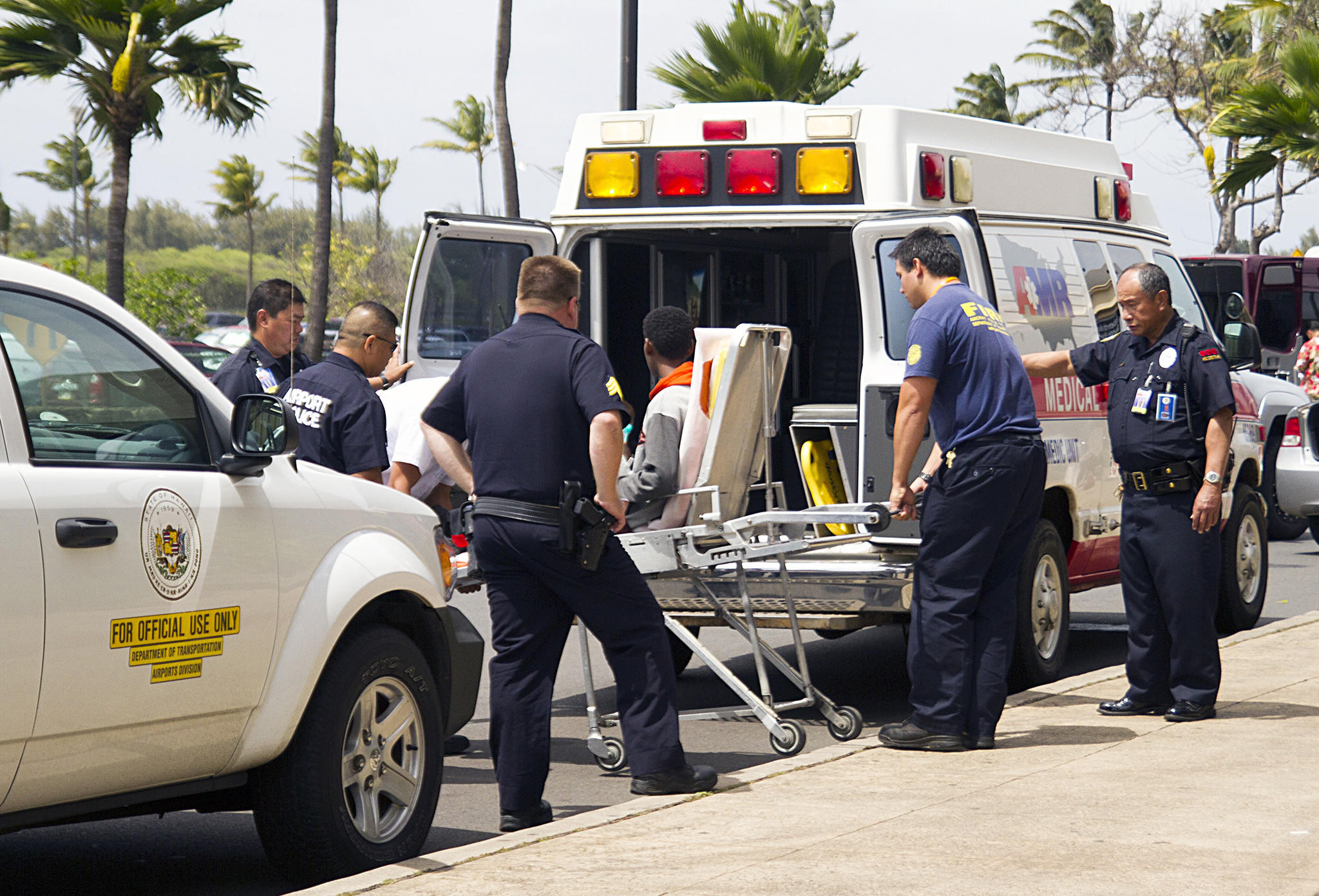 "A 16-year-old boy who stowed away in the wheel well of a flight from California to Hawaii, shown on stretcher at center, is loaded into an ambulance at Kahului Airport in Maui on Sunday afternoon. Officials say the boy is unharmed and ""lucky to be alive,"" having survived hypoxia and hypothermia."