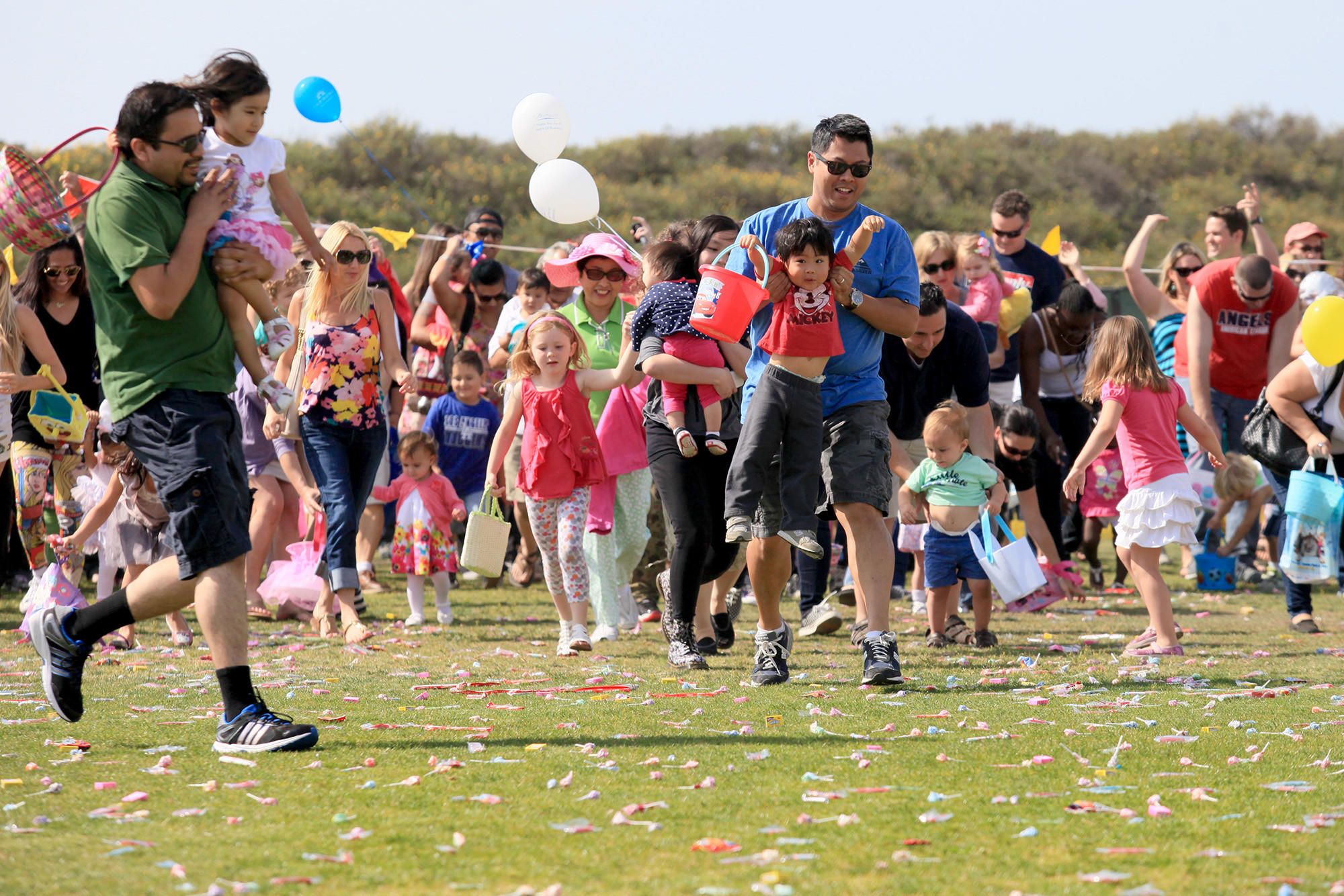 Parents and children rush out to collect candy during an annual Easter egg hunt at Huntington Beach Sports Complex on Saturday.