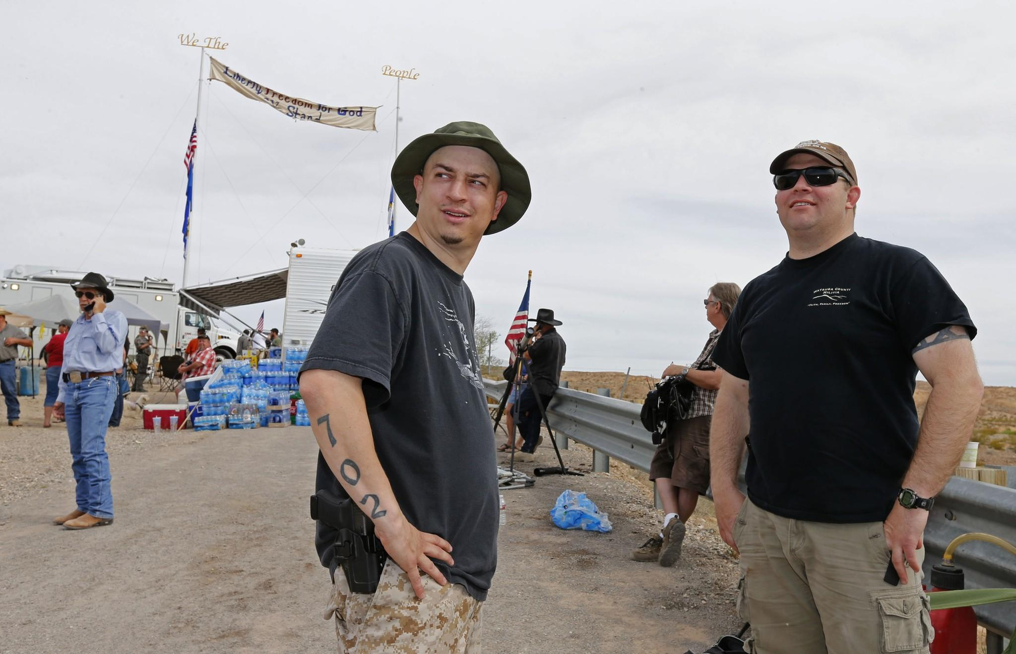 With a sidearm strapped to his side, Anthony Herrea, left, and an unidentified person stand along a protest area along U.S. 170 on April 11 west of Mesquite, Nev.
