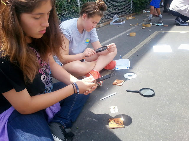"Ellie Escobar and Saku Yoshioka, both 12, and students at Woodrow Wilson Middle School, use magnifying glasses to etch artwork into pieces of wood. Escobar said she learned from the activity that ""the sun can power anything electricity can."""