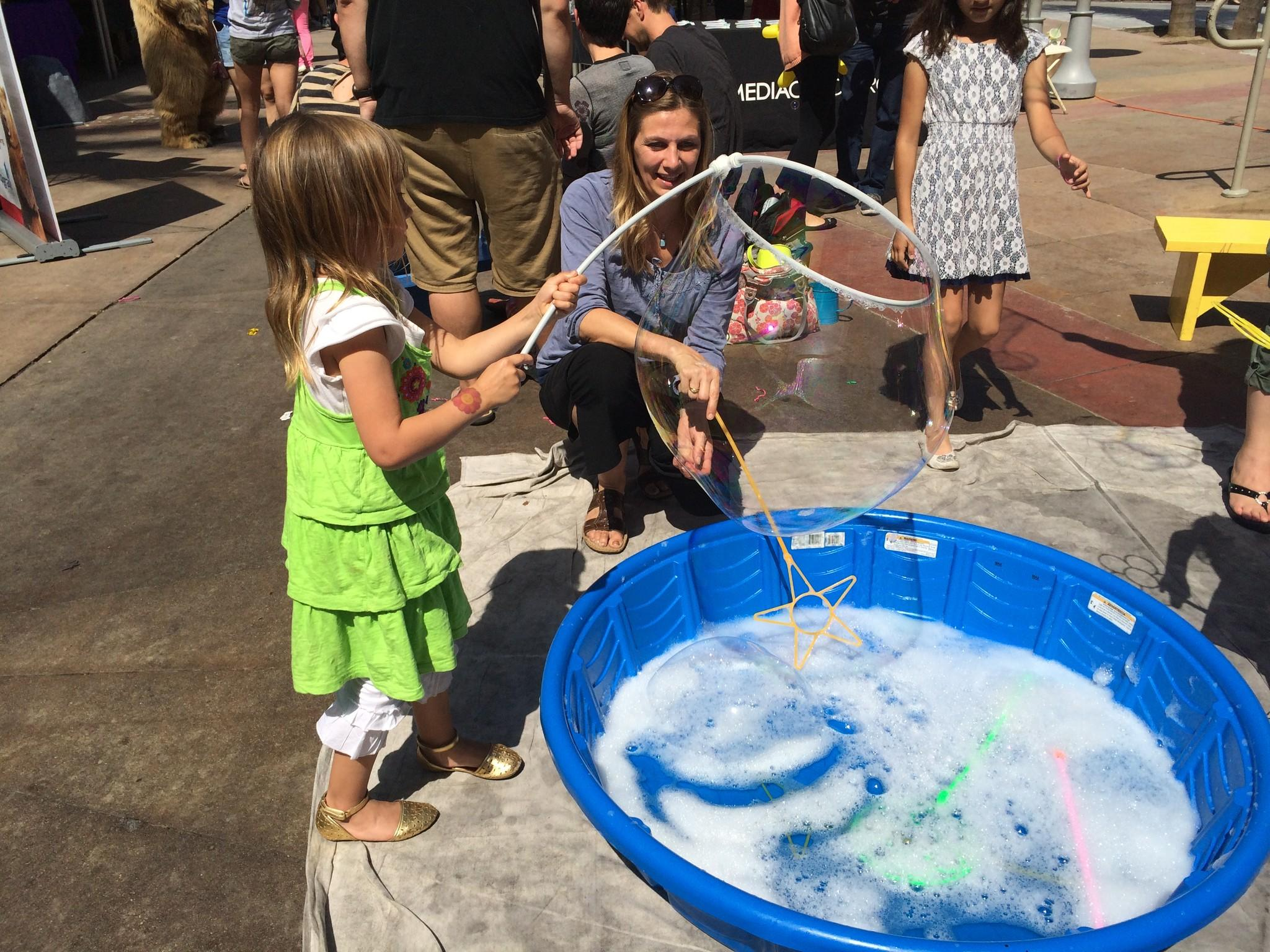 Sienna Euliss, 5, makes a giant bubble at the Downtown Burbank Arts Festival as her mother, Ulrika, watches.