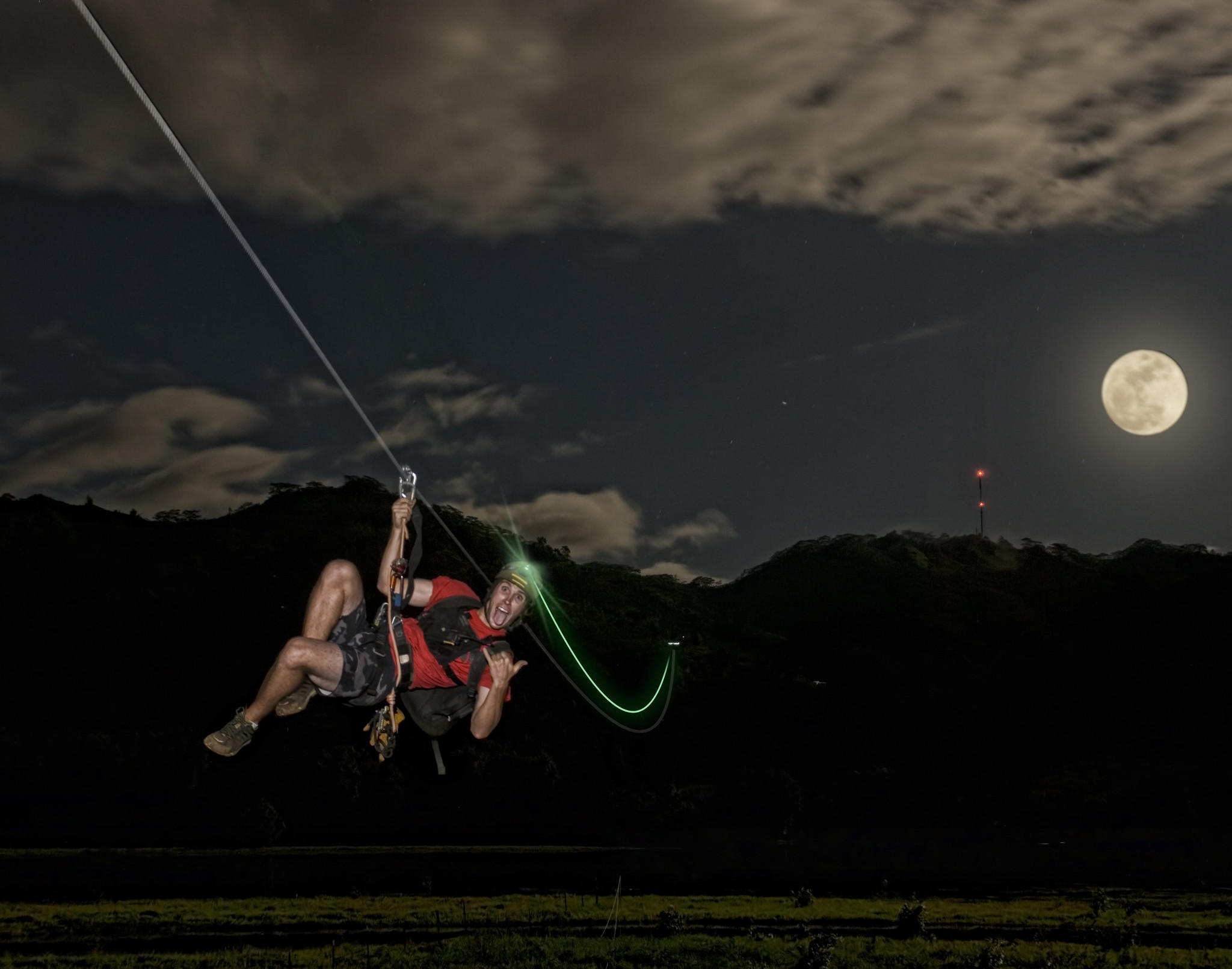 The glow of a headlamp leaves an eerie trail as a guest crosses the longest of eight lines during the Sunset Zip attraction on Kauai.