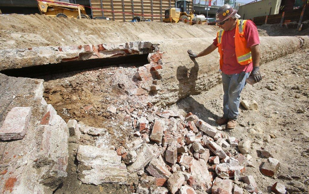 "Construction worker Carlos Andrade examines a section of Los Angeles' early water system, the Zanja Madre, or ""Mother Ditch,"" which was discovered by workers excavating the site of a Chinatown development on North Spring Street"