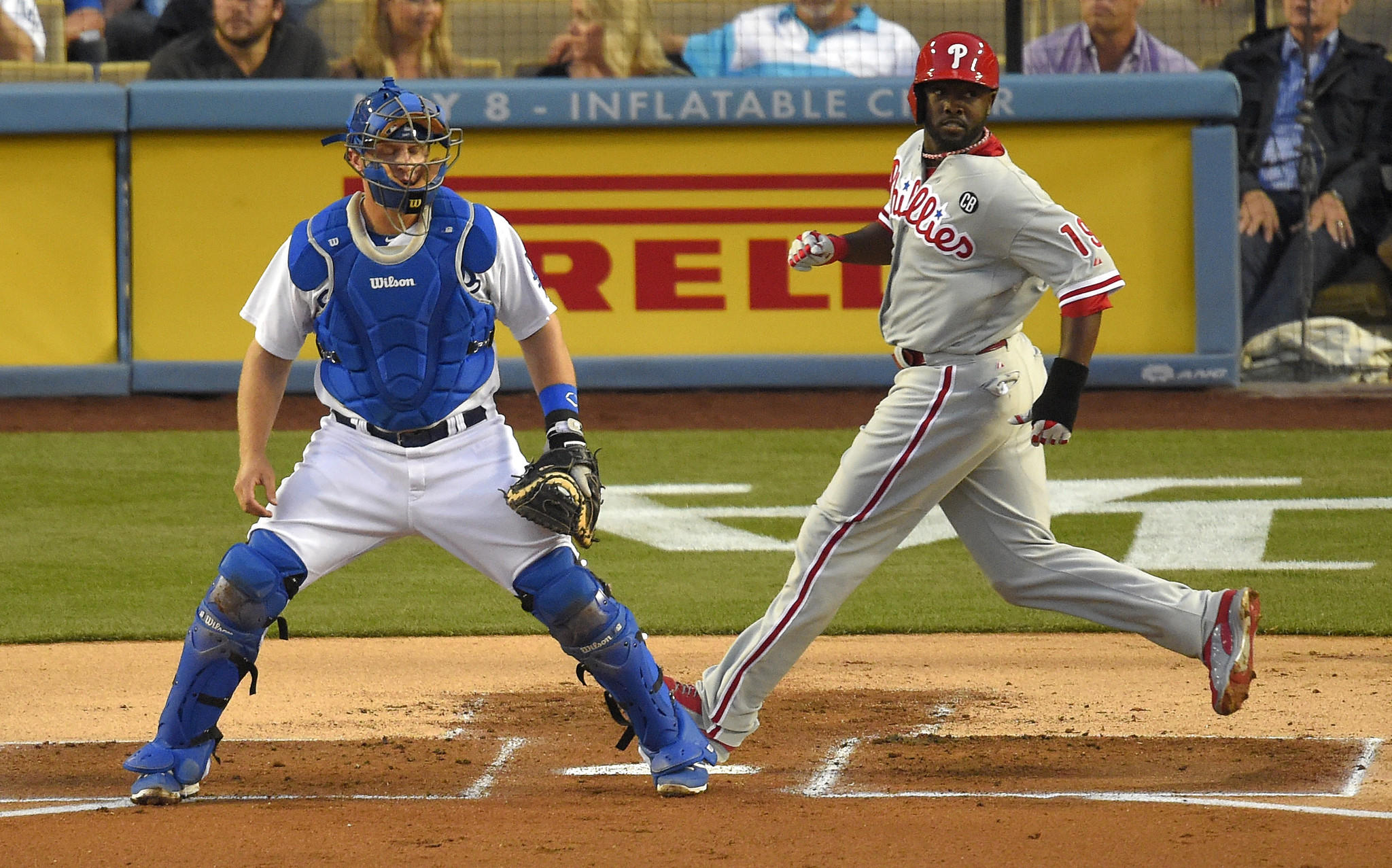 Philadelphia Phillies center fielder Tony Gwynn Jr., right, scores next to Dodgers catcher Tim Federowicz on a double by Carlos Ruiz in the first inning of the Dodgers' 7-0 loss Monday at Dodger Stadium.