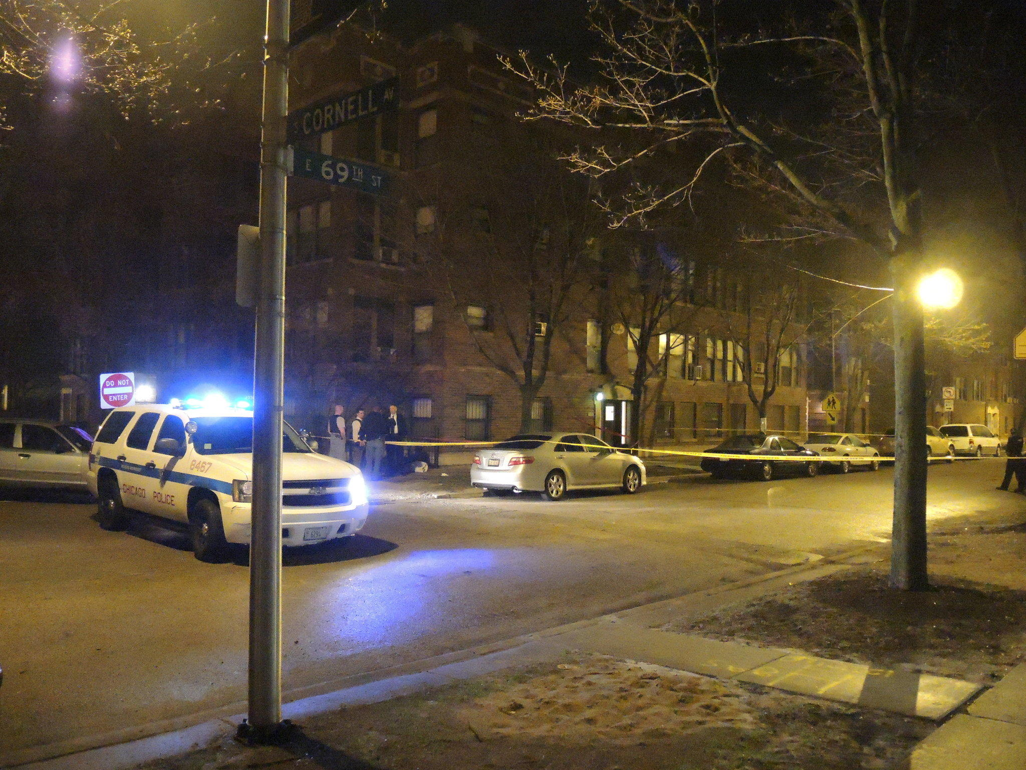 A group of police officers stand at the edge of a crime scene in the 1600 block of East 69th Street late Monday night.