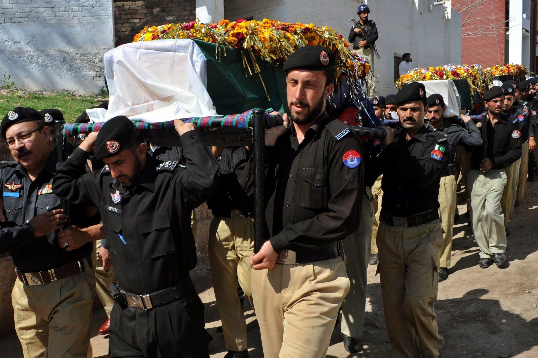 Pakistani security officials carry the coffins of police officers killed in a suspected militant attack the day before near Peshawar.