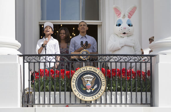 President Obama, First Lady Michelle Obama and the Easter Bunny stand with their hands on their hearts as Cam Anthony sings the national anthem at the annual White House Easter Egg Roll on Saturday.