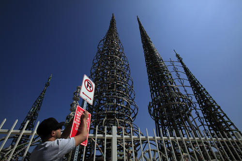 "Street artist Jason Shelowitz (a.k.a. Jay Shells) installs a sign at Watts Towers featuring rap lyrics by Crooked I: ""Got street power from the Watts Towers to Howard Hughes. How would you become me I don't Do what you cowards do."""