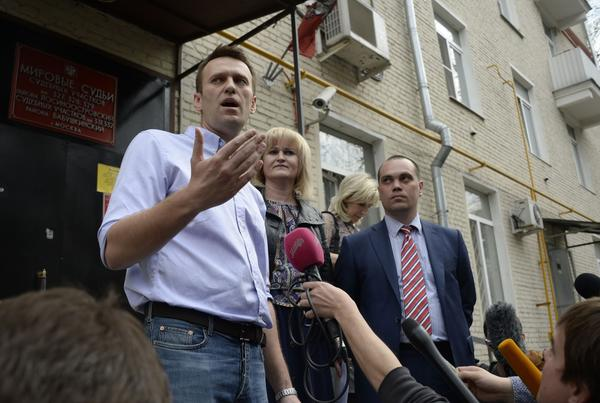 Kremlin critic and opposition leader Alexei Navalny speaks with journalists outside a courthouse in Moscow on Tuesday after his conviction on slander charges. Navalny, under house arrest for the last two months, had a previous five-year sentence tied to his anti-corruption crusading suspended last year on condition he not run afoul of the law. He is likely to be returned to prison soon.