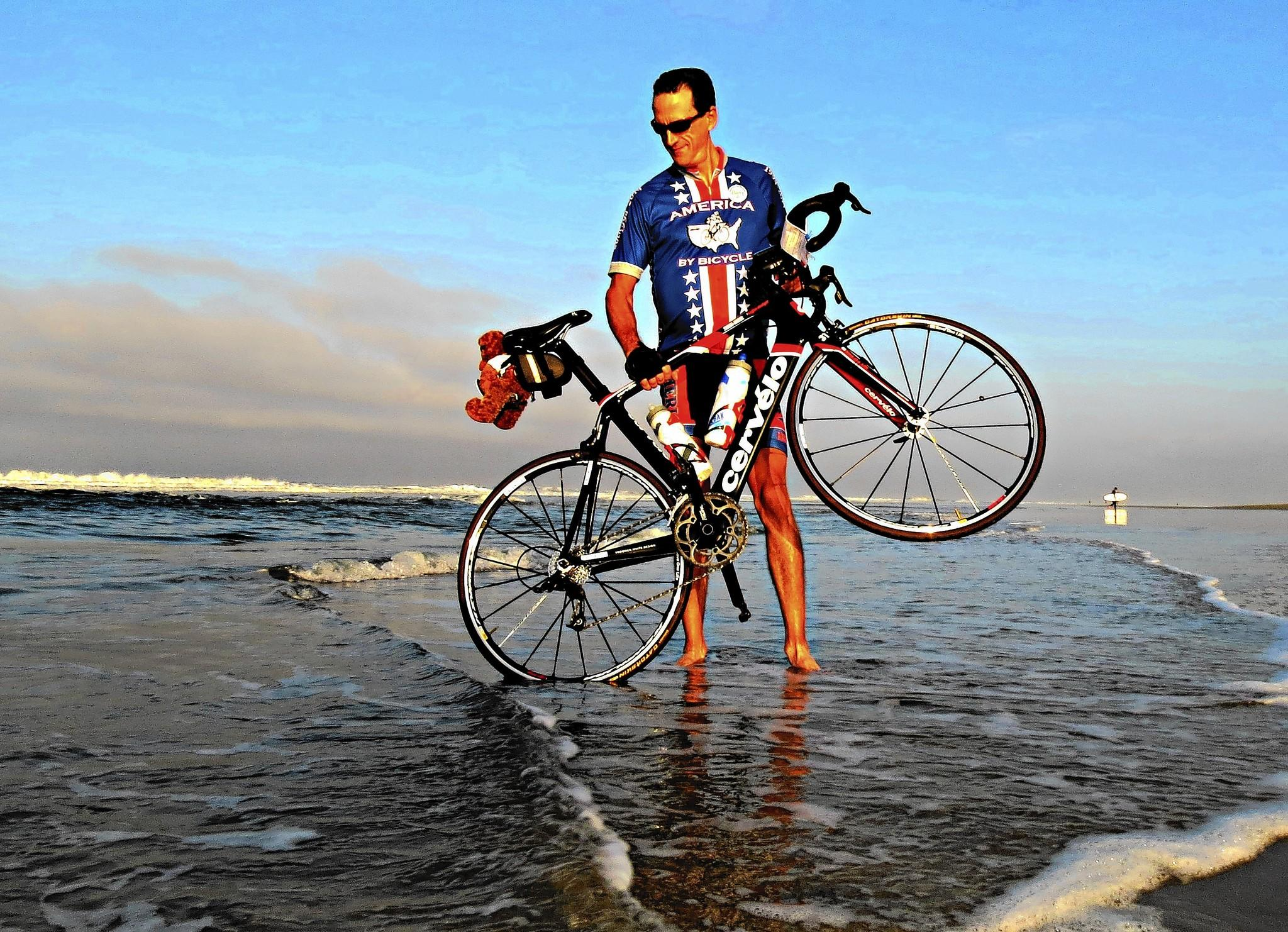 Barry Haarde dips the wheel of his bike into the Pacific Ocean before embarking on his third cross-country ride.