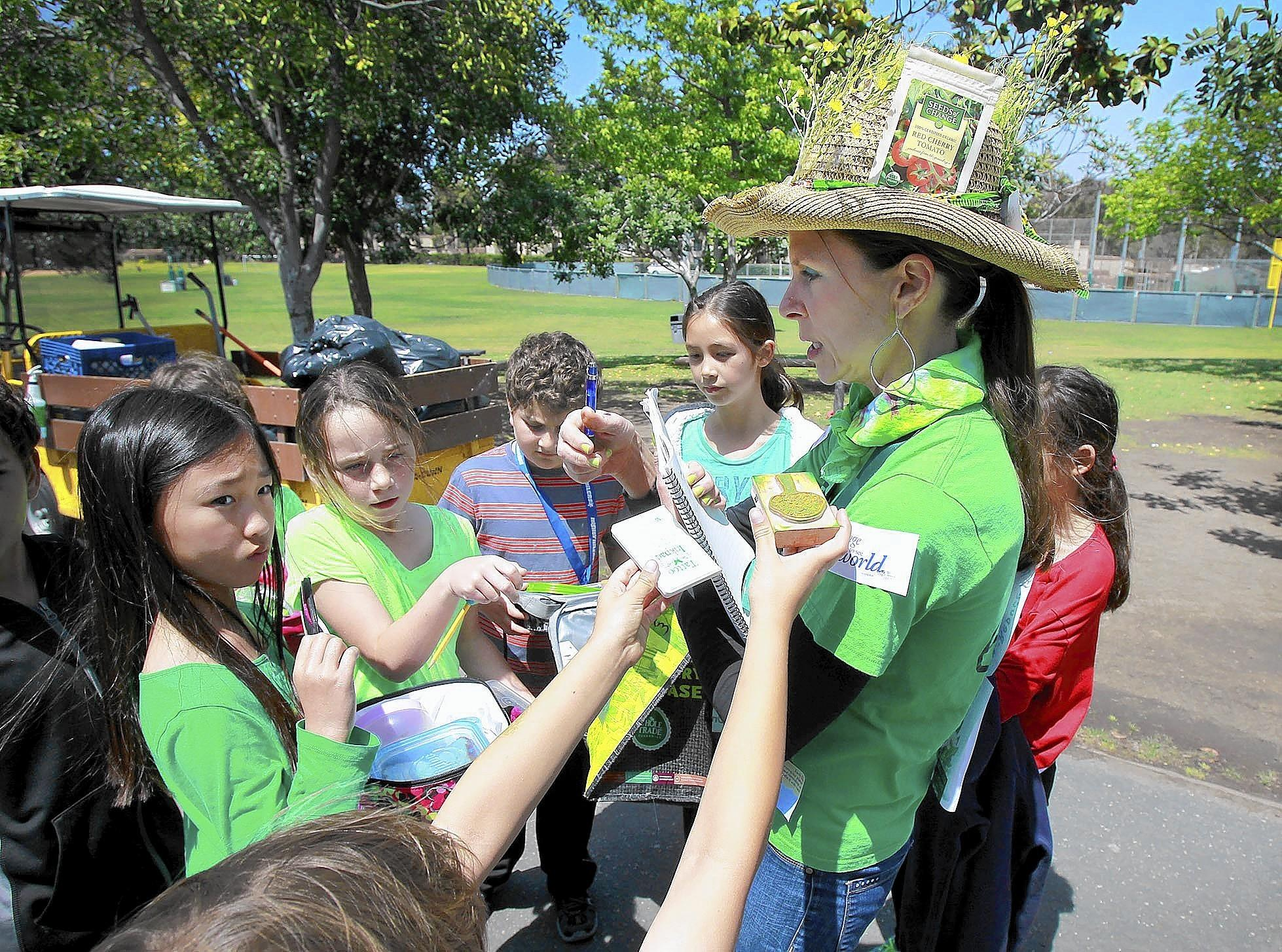 Parent volunteer Cherie Hemphill, wearing a straw hat decorated like a garden, is mobbed by kids who look to get an award stamp for bringing a trash-free lunch to school during Earth Day recognition at Lincoln Elementary on Tuesday.