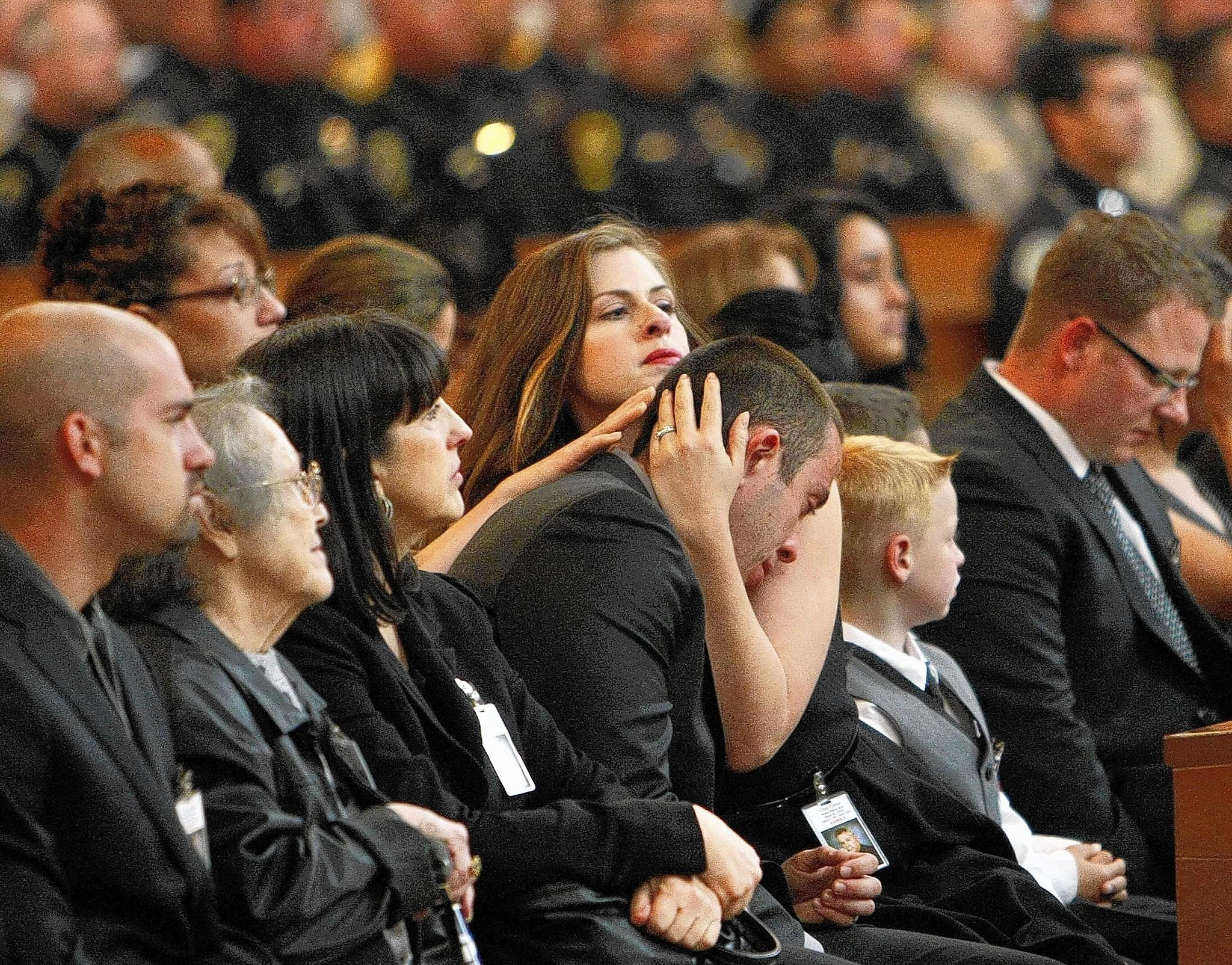 Christina Beal and Jonathan Cortijo, daughter and son of LAPD Officer Christopher A. Cortijo, after speaking at their father's funeral Mass at the Cathedral of Our Lady of the Angels in downtown Los Angeles.