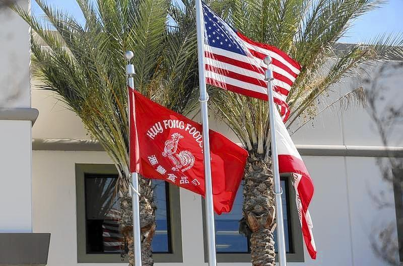 Flags flutter outside the Huy Fong Foods factory, maker of Sriracha hot chili sauce, in Irwindale, California.