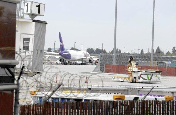 A worker moves equipment near gates used by Hawaiian Airlines at Norman Y. Mineta San Jose International Airport in San Jose.