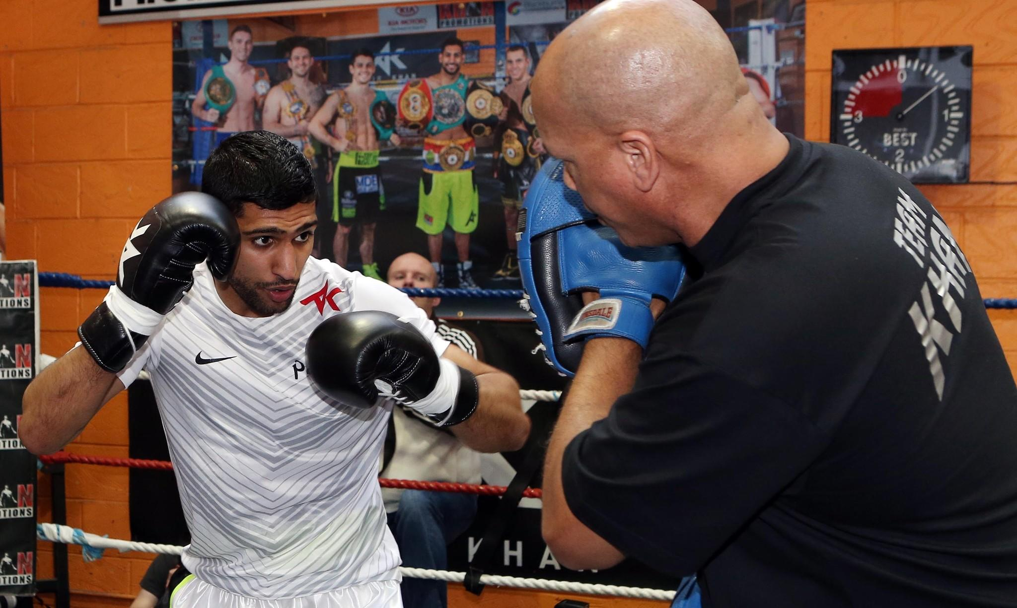 Amir Khan works out with his trainer, Virgil Hunter, in Bolton, England, on March 24.