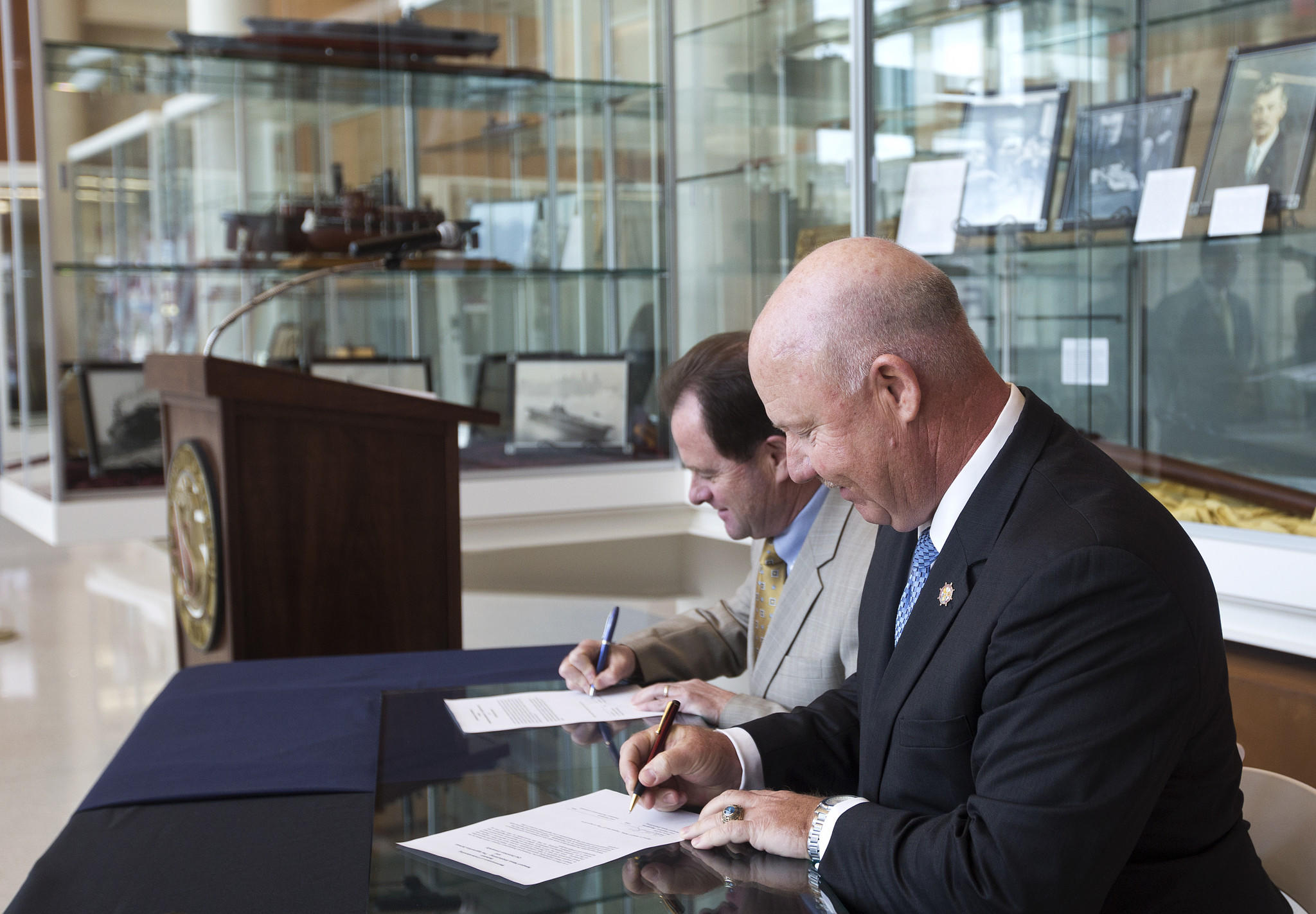 John Broderick, president of Old Dominion University, left, and Danny Hunley, vice president of operations at Newport News Shipbuilding, right, sign a memorandum for a new partnership to offer students an engineering apprenticeship program.