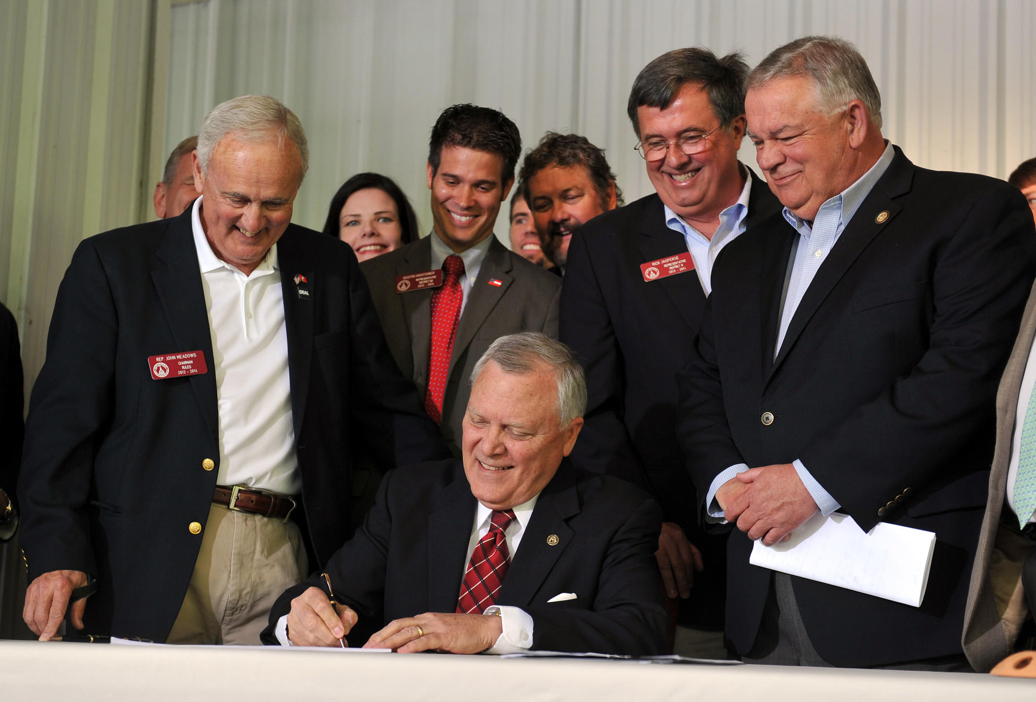 Surrounded by supporters of the legislation, Georgia Gov. Nathan Deal signs House Bill 60 into law Wednesday. The bill makes several changes to the state's gun laws.