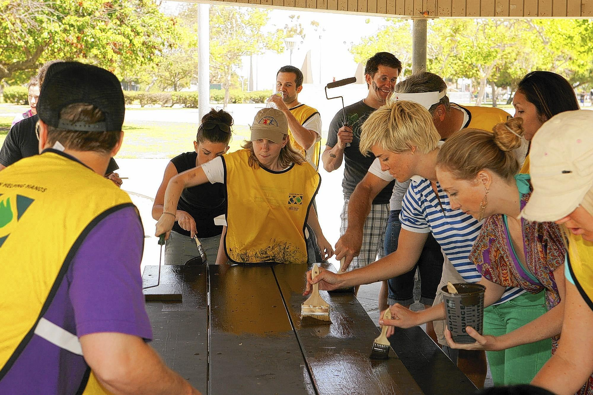 Volunteers with the Church of Jesus Christ of Latter-day Saints repaint a table at the Edison Community Center last year. The Mormon Church is teaming up with the Greater Huntington Beach Interfaith Council on Saturday for the Compassionate Day of Community Service.