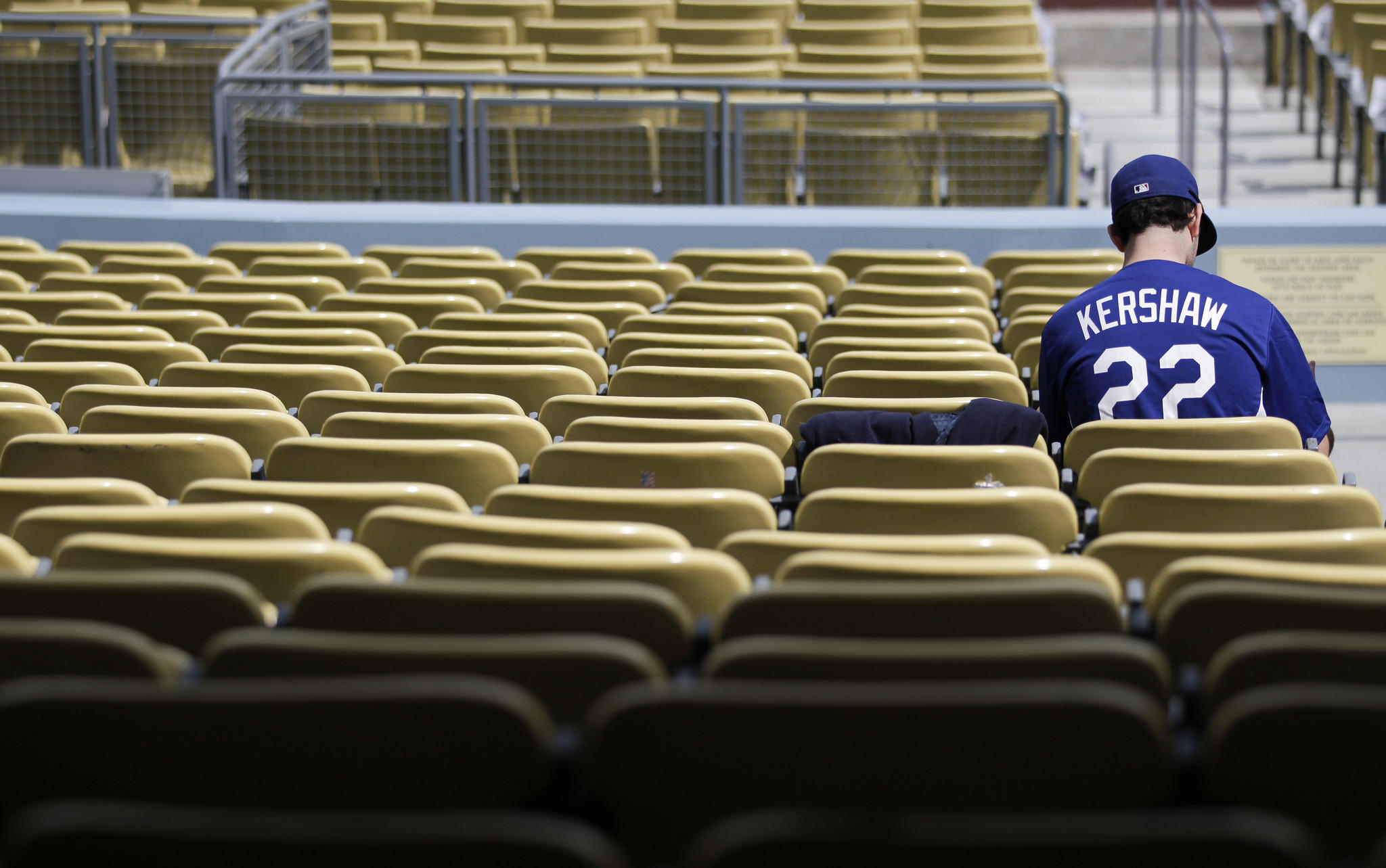 A fan wearing a t-shirt bearing the name of Dodgers ace Clayton Kershaw sits in the field-level seats at Dodger Stadium before the team's home opener against the San Francisco Giants. Some fans upset by the Dodgers' ongoing television debacle have threatened to boycott the team.