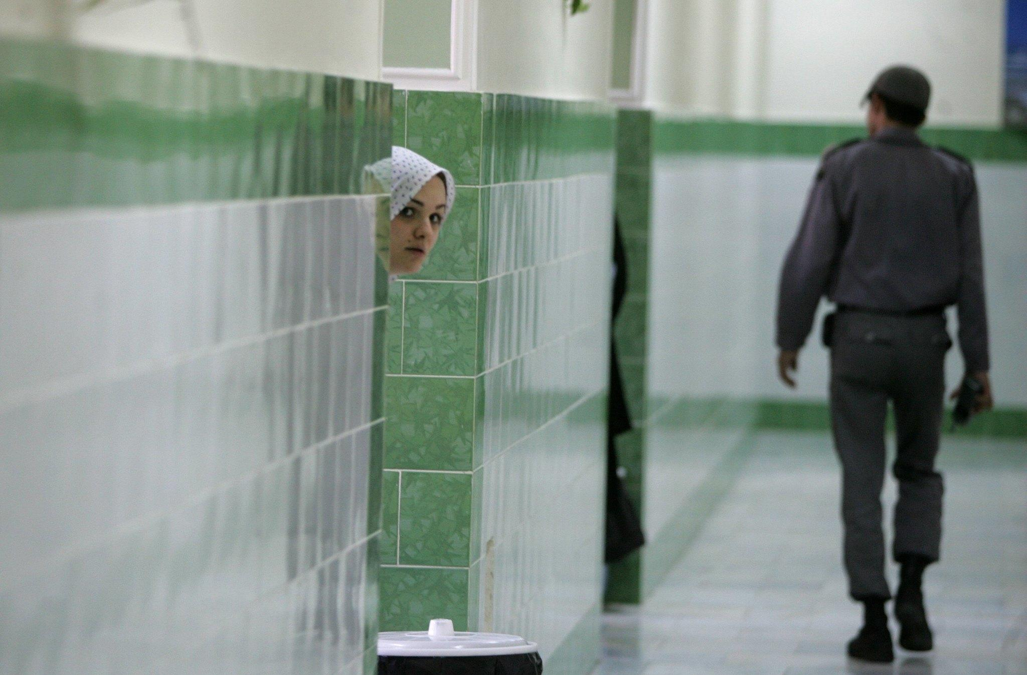 An inmate peers out as a guard passes in the female section of Evin Prison, north of Tehran, in June 2006.