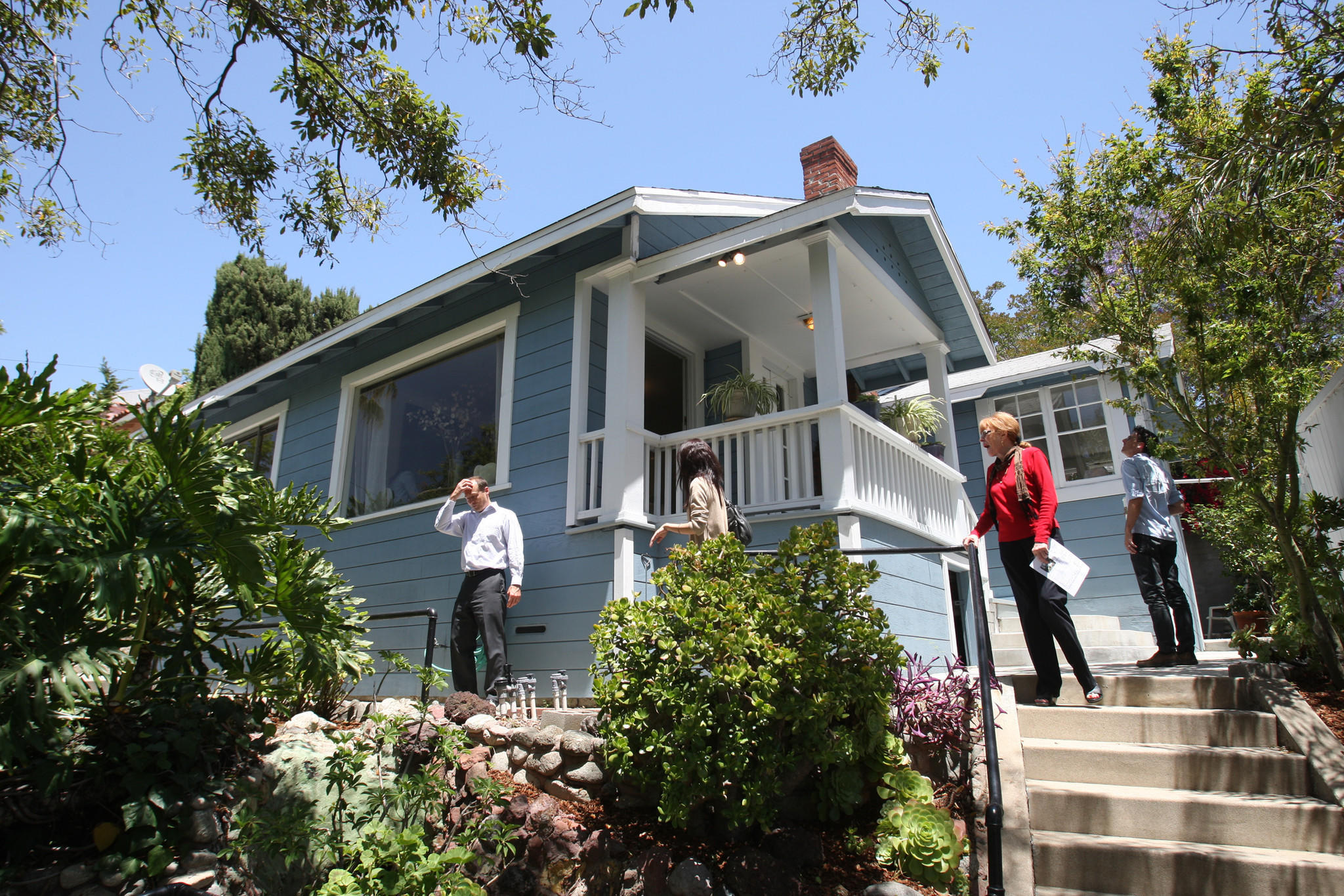 Homes are staying on the market longer in Southern California this spring. Here, prospective buyers tour a house in Highland Park.