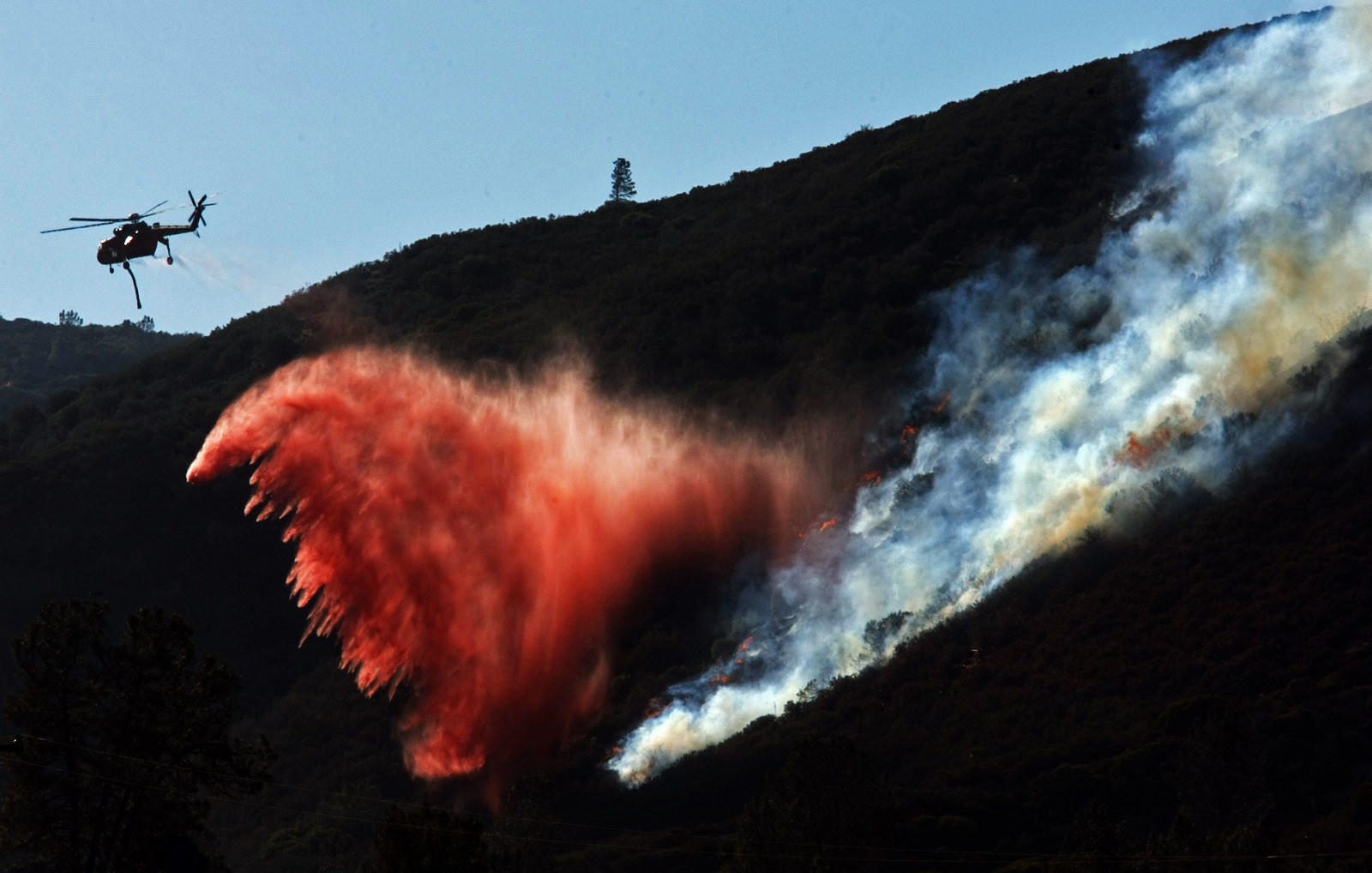 A helicopter drops fire retardant on a ridge near Lake Hughes where the Powerhouse Fire burned last summer. Plaintiffs alleging they suffered damages in the fire are suing the L.A. County DWP.