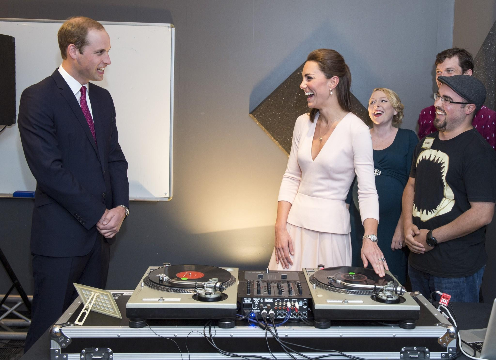 Catherine, Duchess of Cambridge and Prince William, Duke of Cambridge laugh as they are shown how to play on DJ decks at the Northern Sound System, a youth community center in a suburb of Adelaide, Australia.