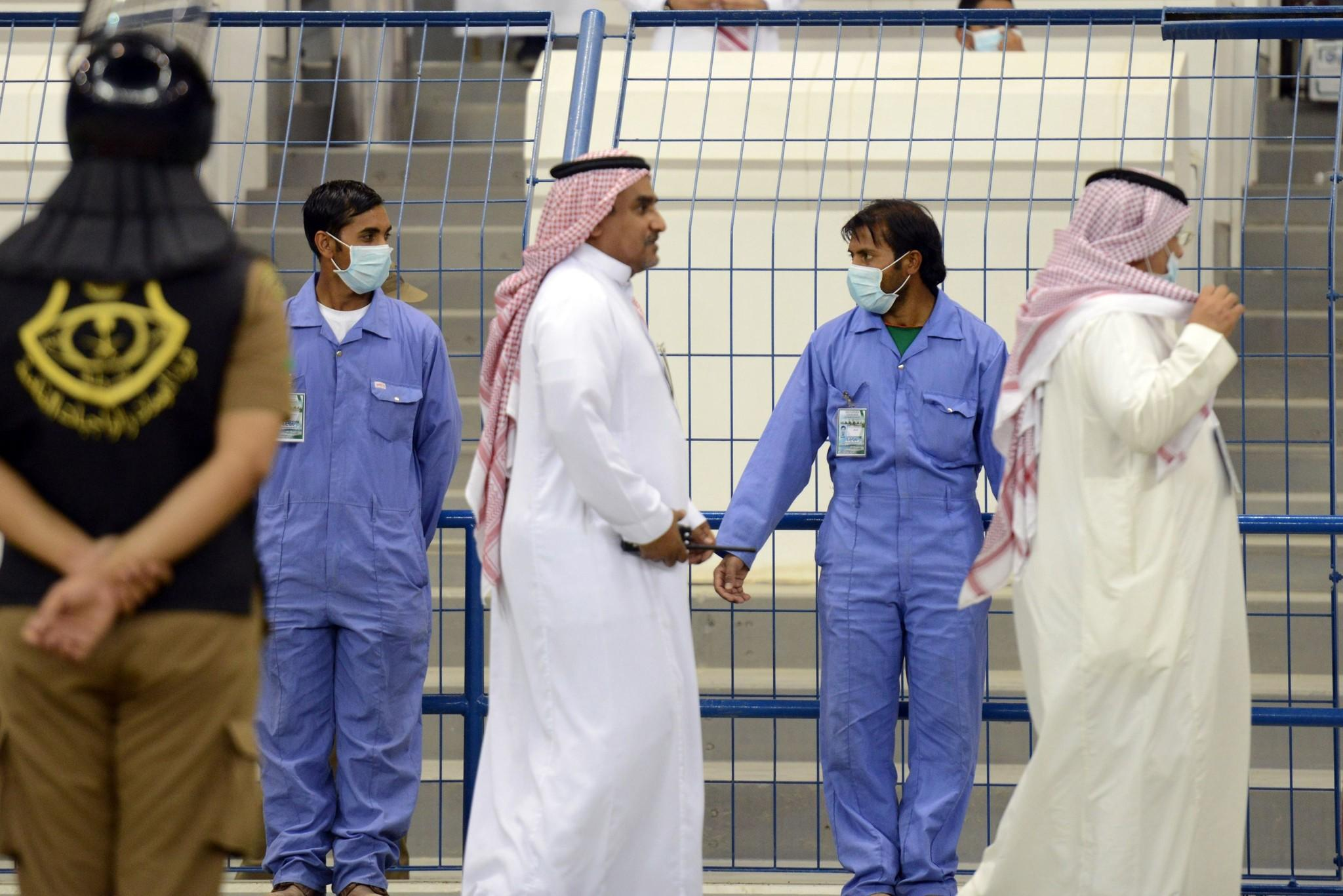 Asian workers wear mouth and nose masks while on duty during a football match at the King Fahad stadium in Riyadh.