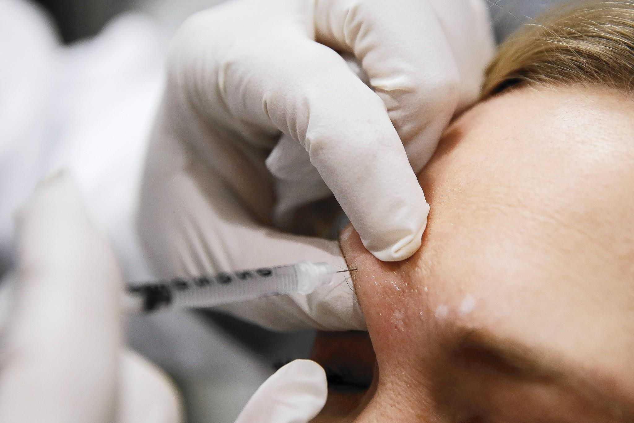 "Dr. Keith A. Marcus injects Botox into a patient's forehead at the offices of Marcus Facial Plastic Surgery in Redondo Beach. Allergan, the maker of Botox, has adopted a ""poison pill"" defense to delay a takeover by Valeant Pharmaceuticals and activist investor Bill Ackman."