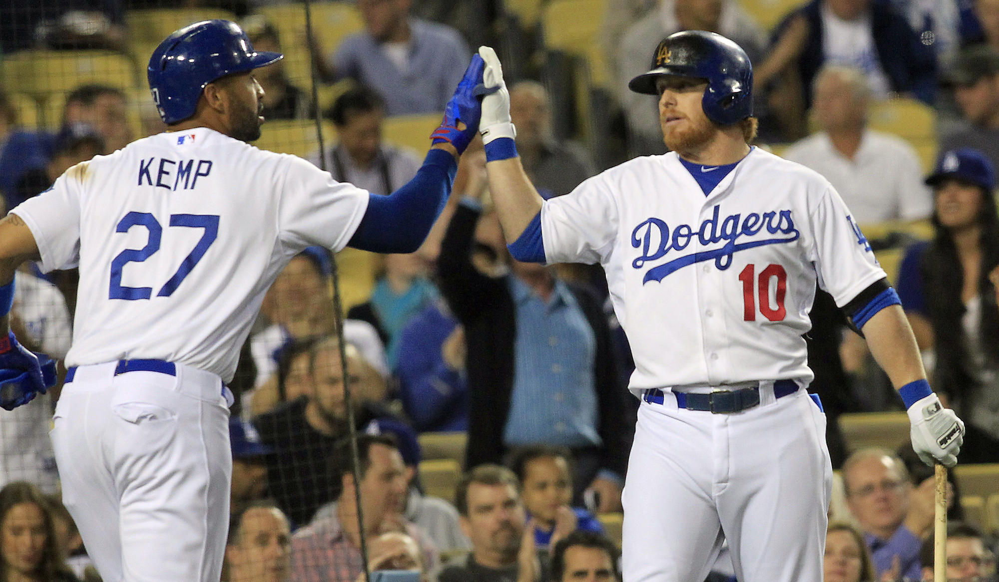 Dodgers center fielder Matt Kemp, left, is congratulated by second baseman Justin Turner after scoring on a sacrifice fly by Juan Uribe (not pictured) during the second inning of the Dodgers' 5-2 win over the Philadelphia Phillies on Wednesday.