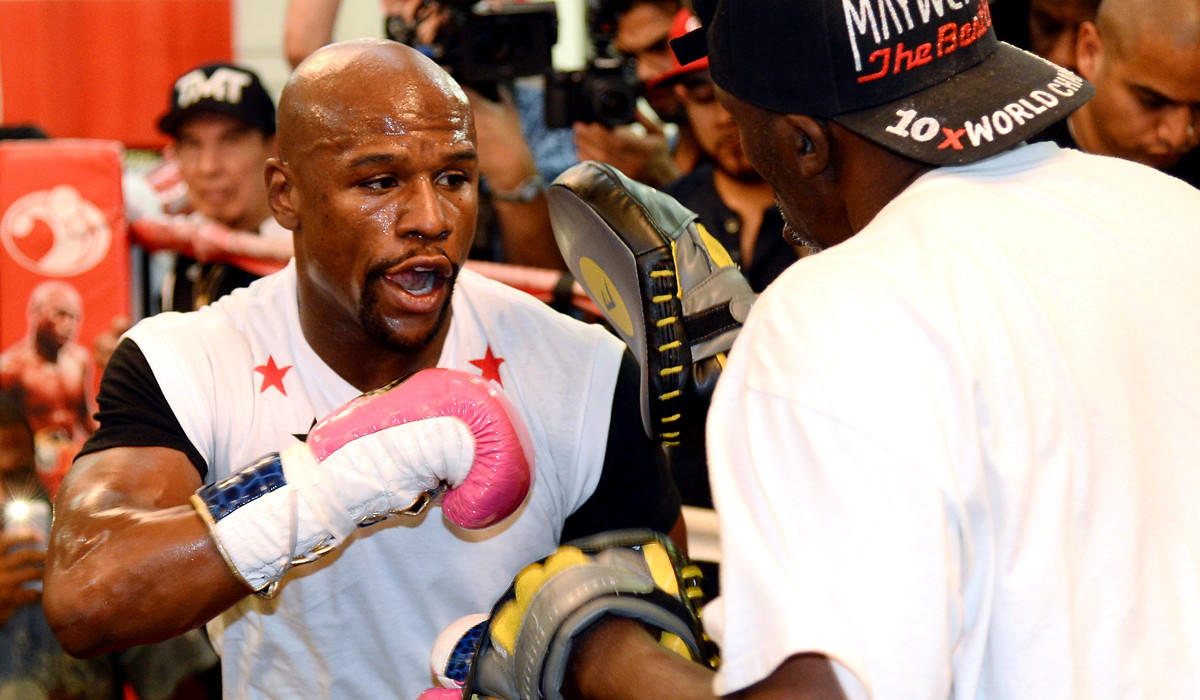 Floyd Mayweather Jr. works out with his trainer and uncle Roger Mayweather at his boxing club in Las Vegas on Tuesday.