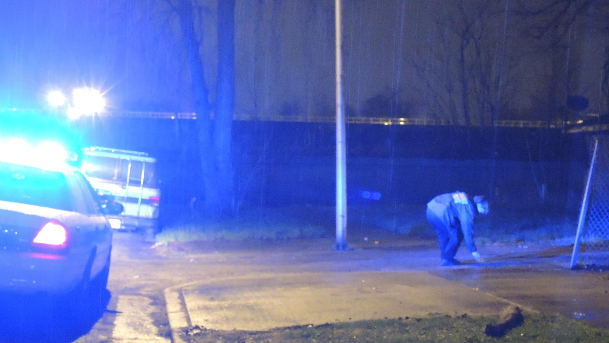 An evidence technician sets out markers next to evidence at a shooting on Lamon Avenue between Hubbard and Kinzie streets.