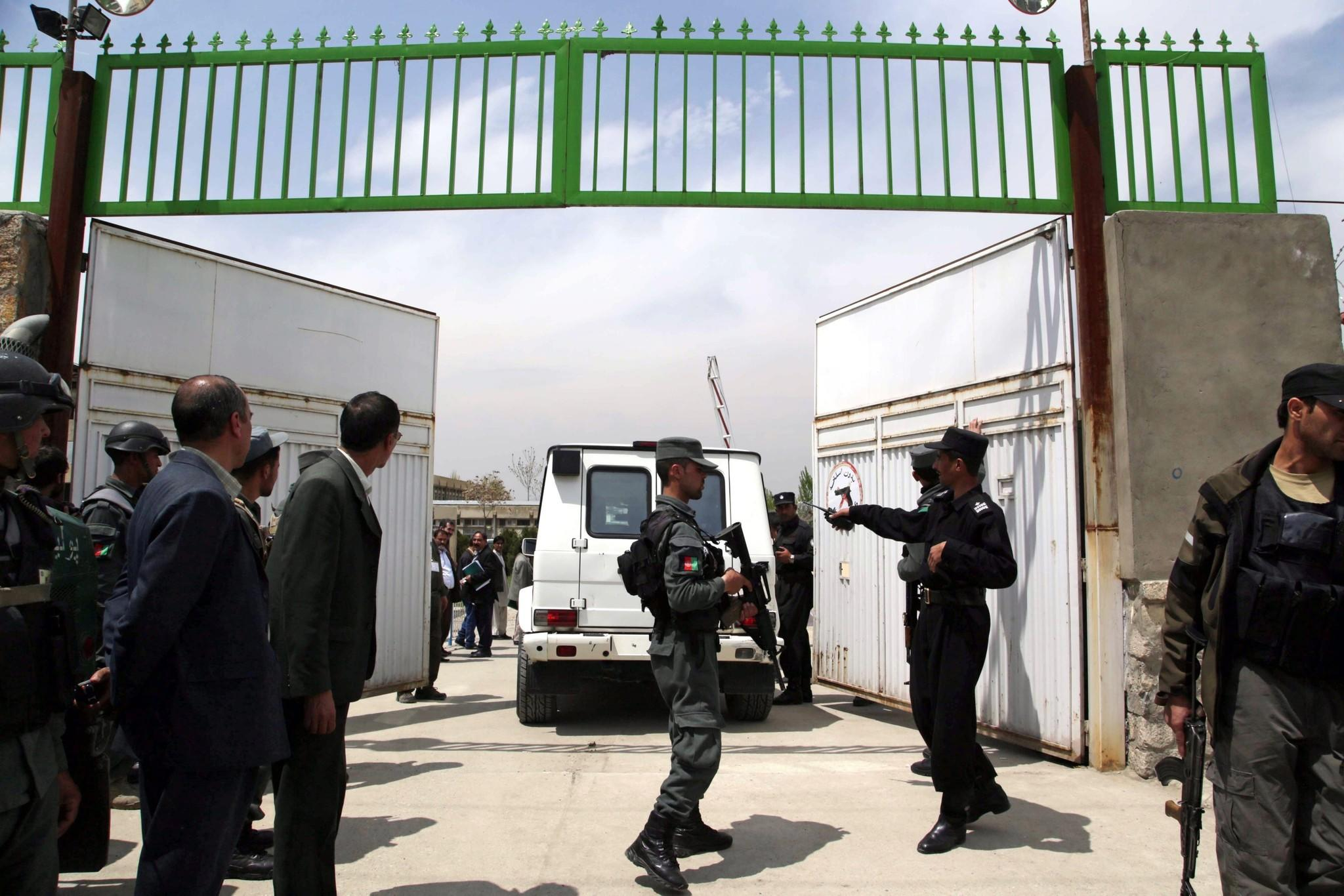 Afghan security officials stand guard outside a Kabul hospital after a guard fatally shot three doctors.