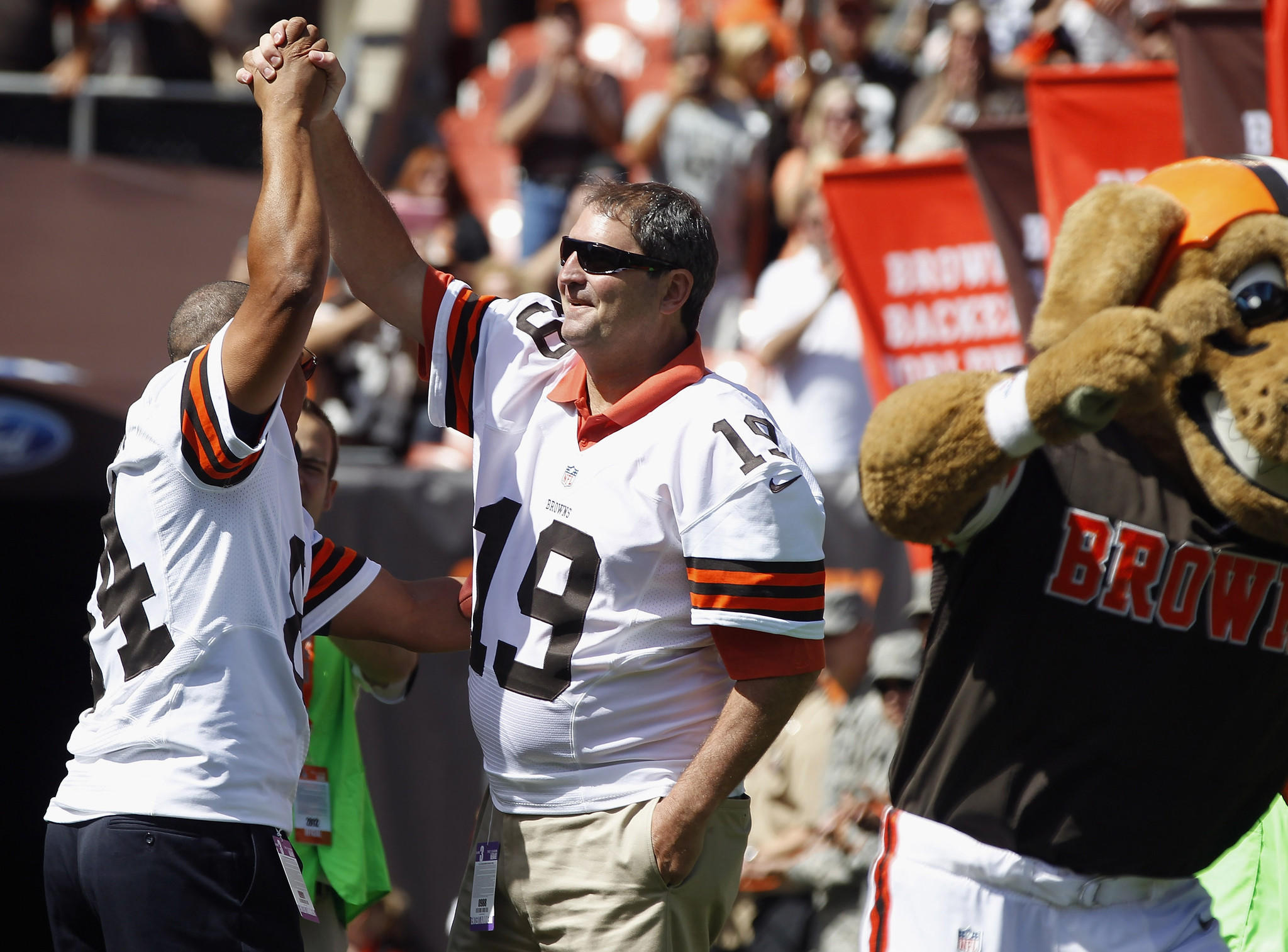 Former Cleveland Browns player Webster Slaughter and Bernie Kosar, right, are honored before the game against the Philadelphia Eagles on Sept. 9, 2012.