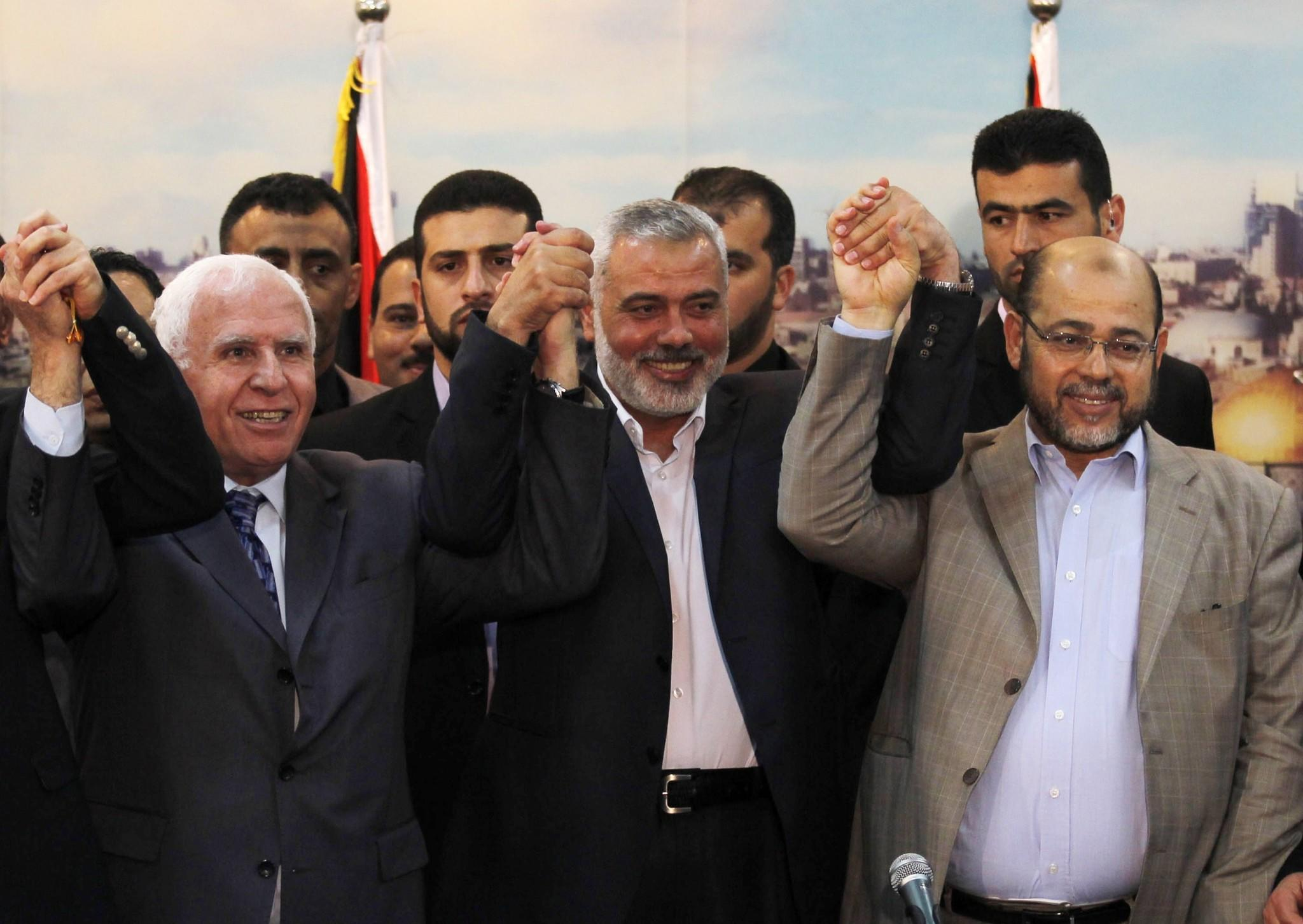 Palestinian Fatah delegation chief Azzam Ahmed, left, Hamas Prime Minister in the Gaza Strip Ismail Haniya and Hamas deputy leader Musa abu Marzuk pose for a photo as they celebrate the Palestinian unity accord Wednesday in Gaza City.
