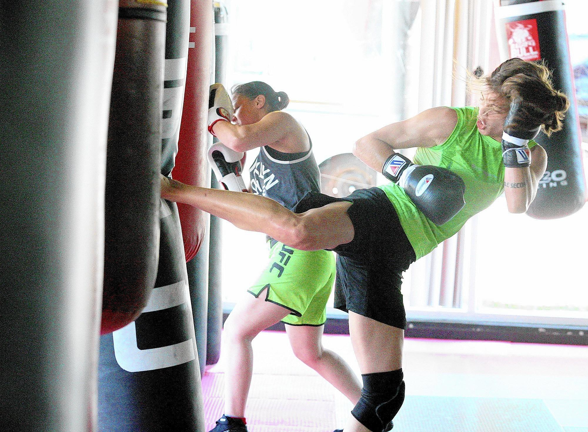 Jessamyn Duke, right, spins and kicks a bag as Shayna Baszler punches a bag as they train at the Glendale Fight Club on Friday, November 1, 2013.