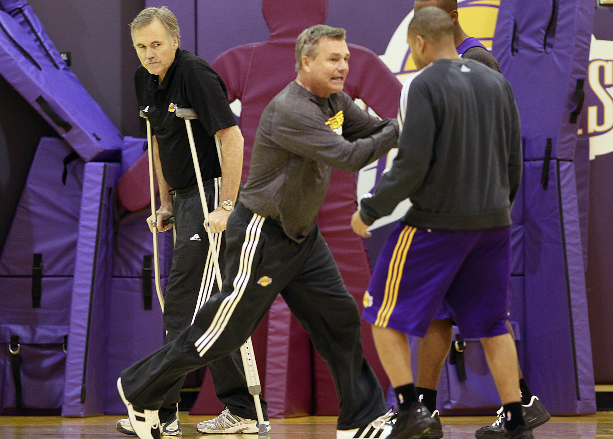 Dan D'Antoni coaches Lakers players during a practice in 2012 while his brother, head coach Mike D'Antoni, watches.