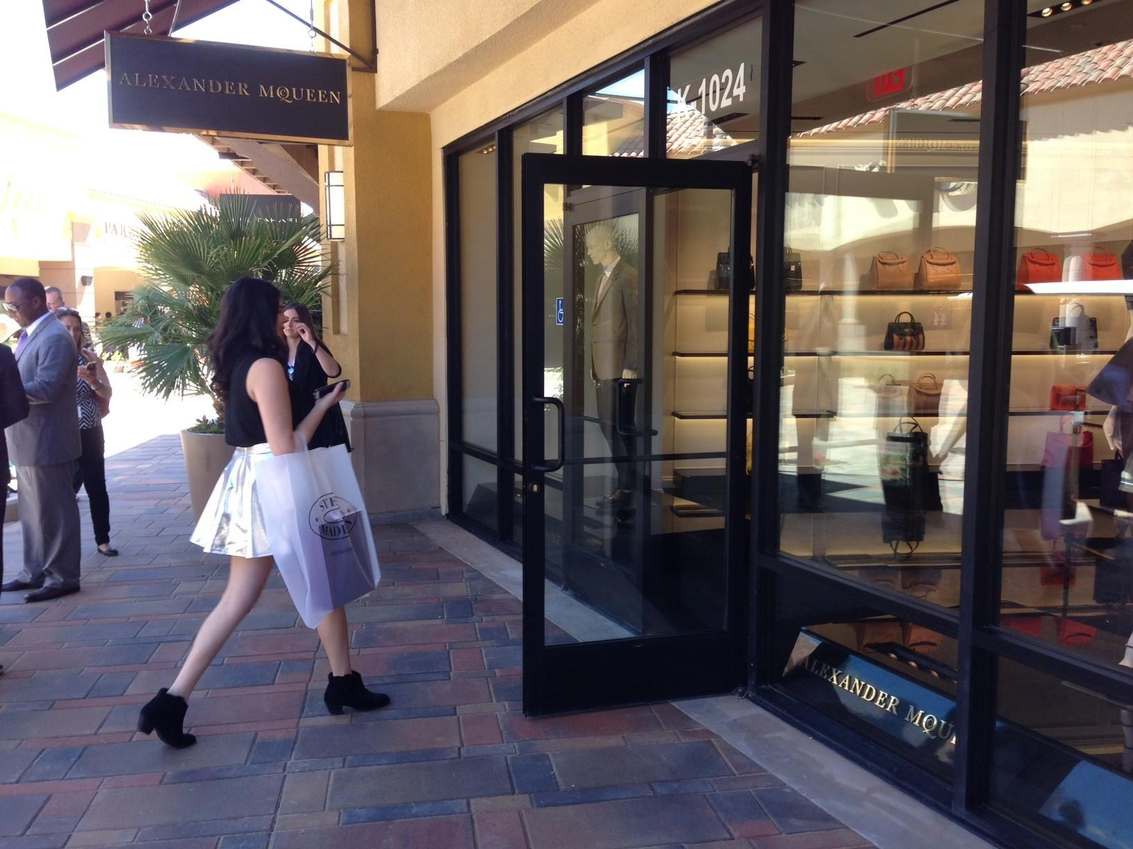 A shopper heads into the new Alexander McQueen store at the Desert Hills outlet mall.