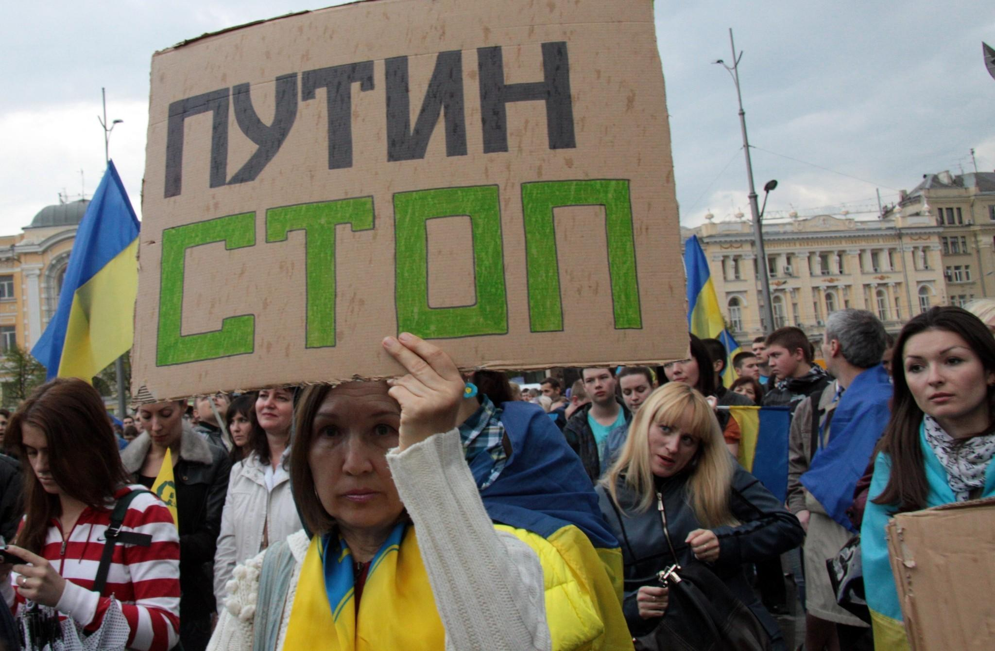 """A woman draped in the Ukrainian flag hoists a sign urging """"Putin Stop"""" during a rally this week that drew 2,000 to show their support for Ukrainian unity in Kharkiv, Ukraine's second-largest city, which has a large Russian minority."""