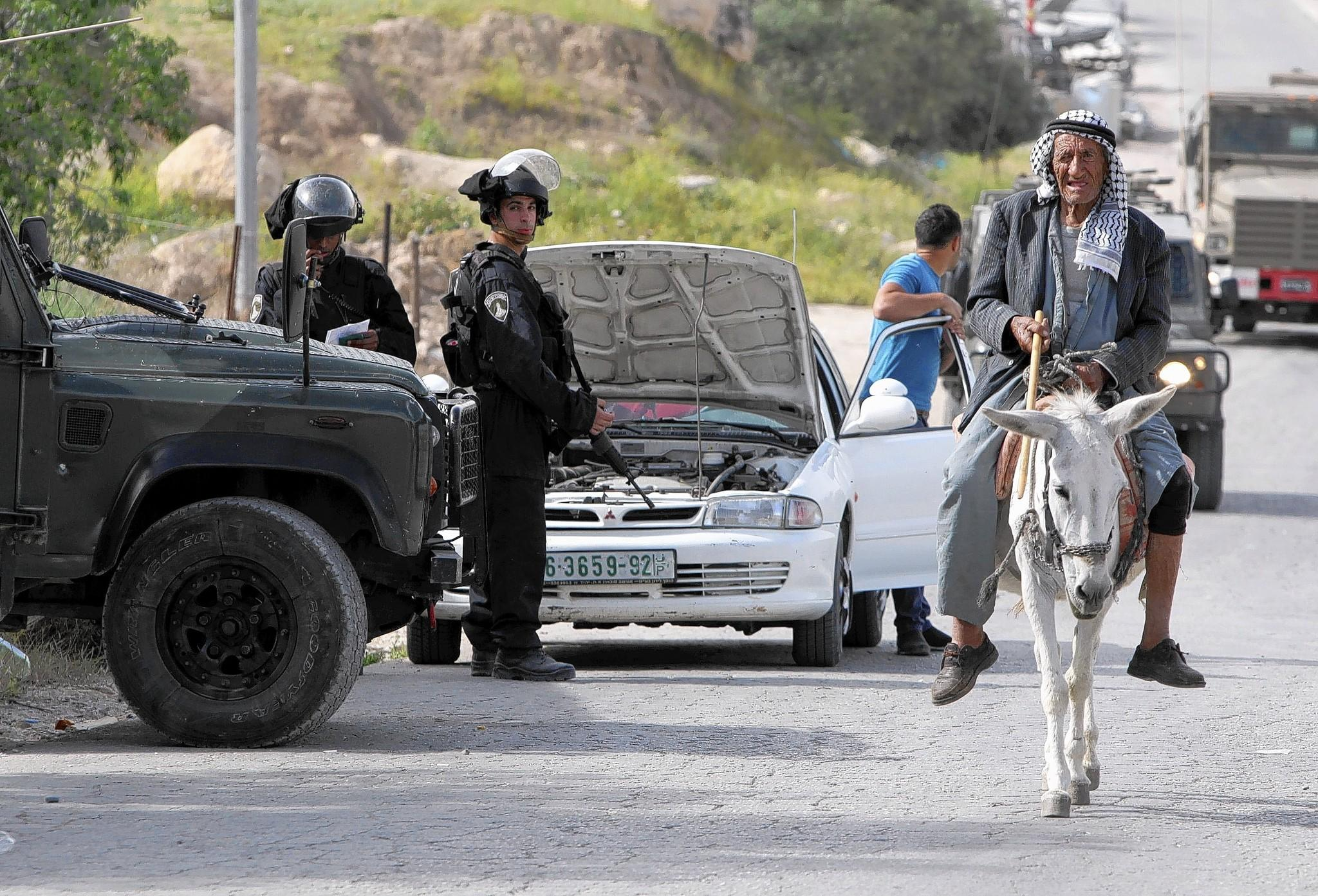 A Palestinian man rides a donkey past Israeli security officers conducting house raids in the West Bank village of Deir Sammit, in the wake of the fatal shooting of a police officer last week.