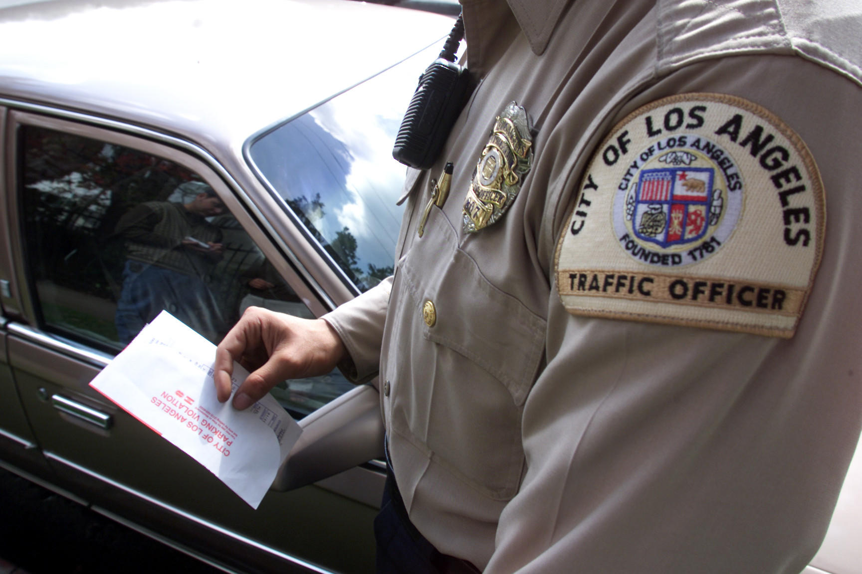 Los Angeles Traffic Officer Manny Garcia writes a parking citation for a car parked in a red zone in the Van Nuys area.