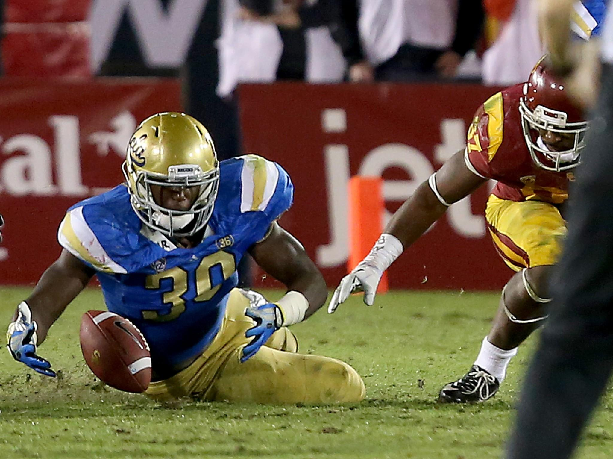 UCLA linebacker Myles Jack recovers a fumble by USC running back Javorius Allen during the Bruins-Trojans rivalry game on Nov. 30.
