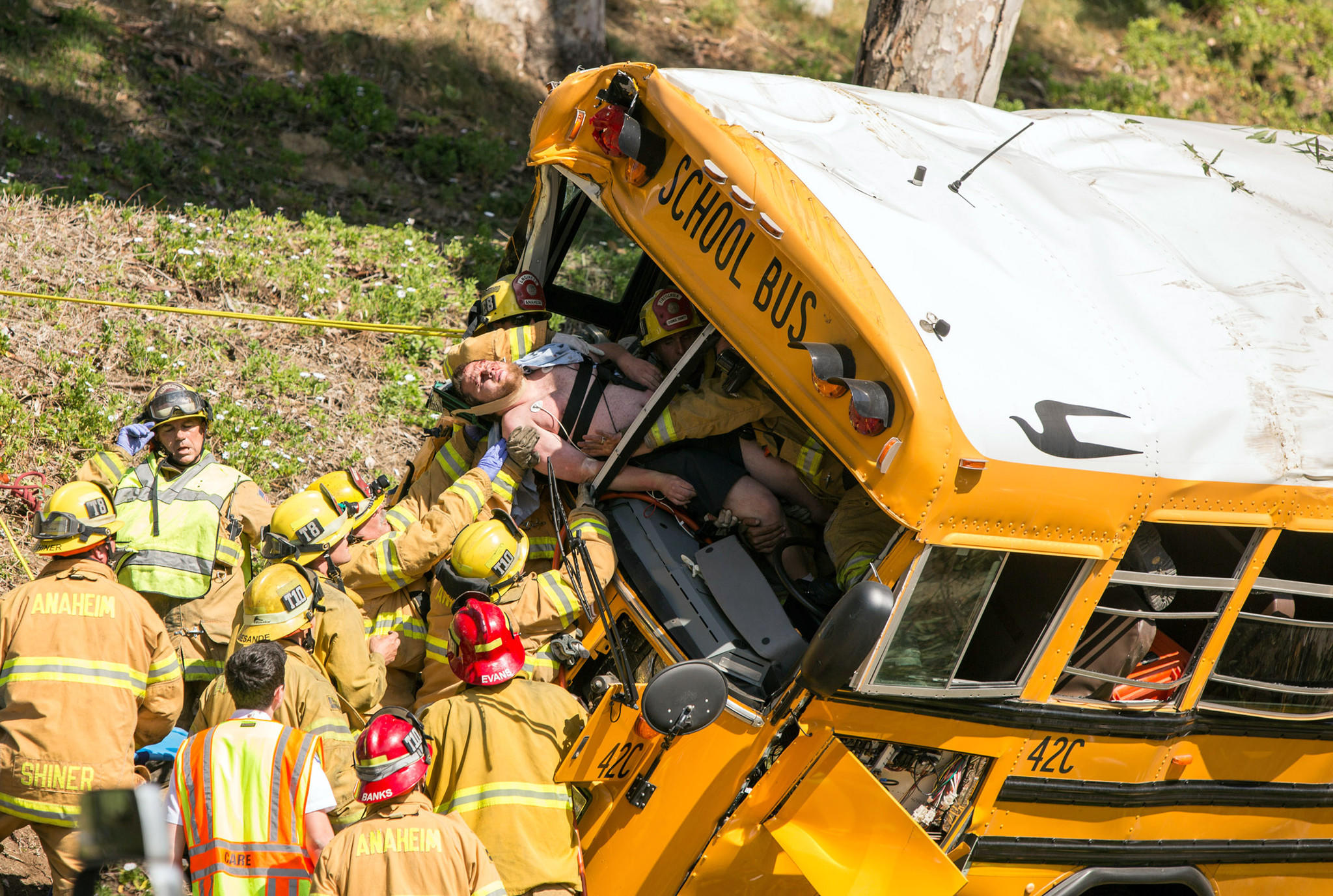 Firefighters pull the driver from the front of a school bus that crashed Thursday in the Anaheim Hills, leaving six people injured, officials say.